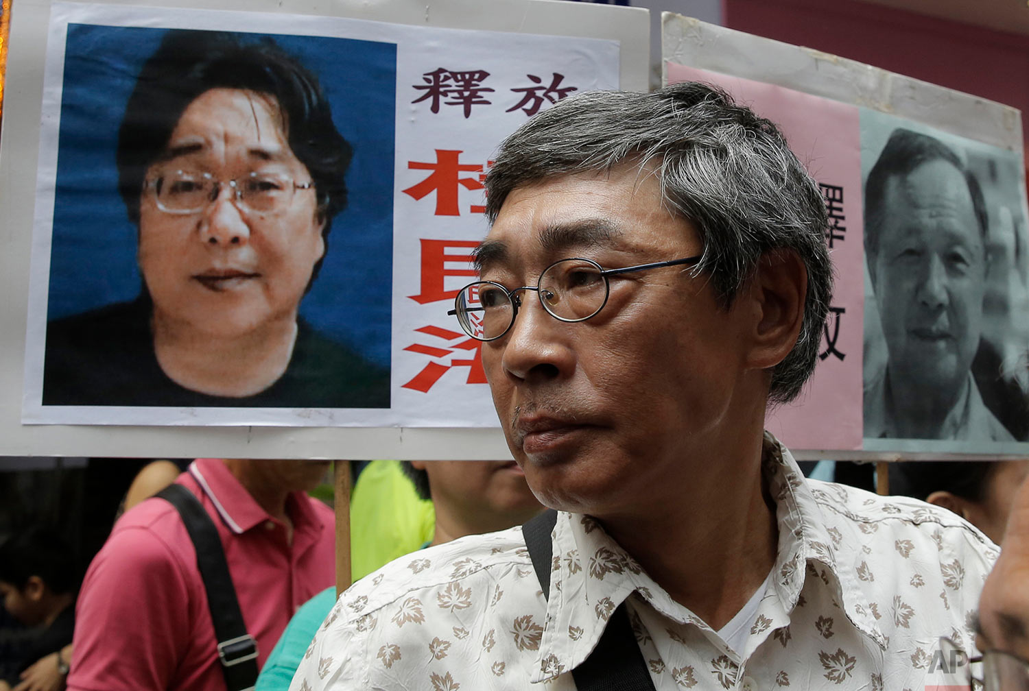Freed Hong Kong bookseller Lam Wing-kee stands next to a placard with picture of missing bookseller Gui Minhai, in front of his book store in Hong Kong, June 18, 2016, as the protesters are marching to the Chinese central government's liaison office. (AP Photo/Kin Cheung)