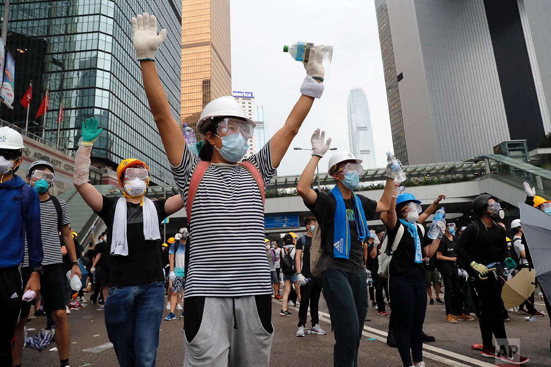 Demonstrators raise their hands near the Legislative Council in Hong Kong, June 12, 2019. (AP Photo/Kin Cheung)