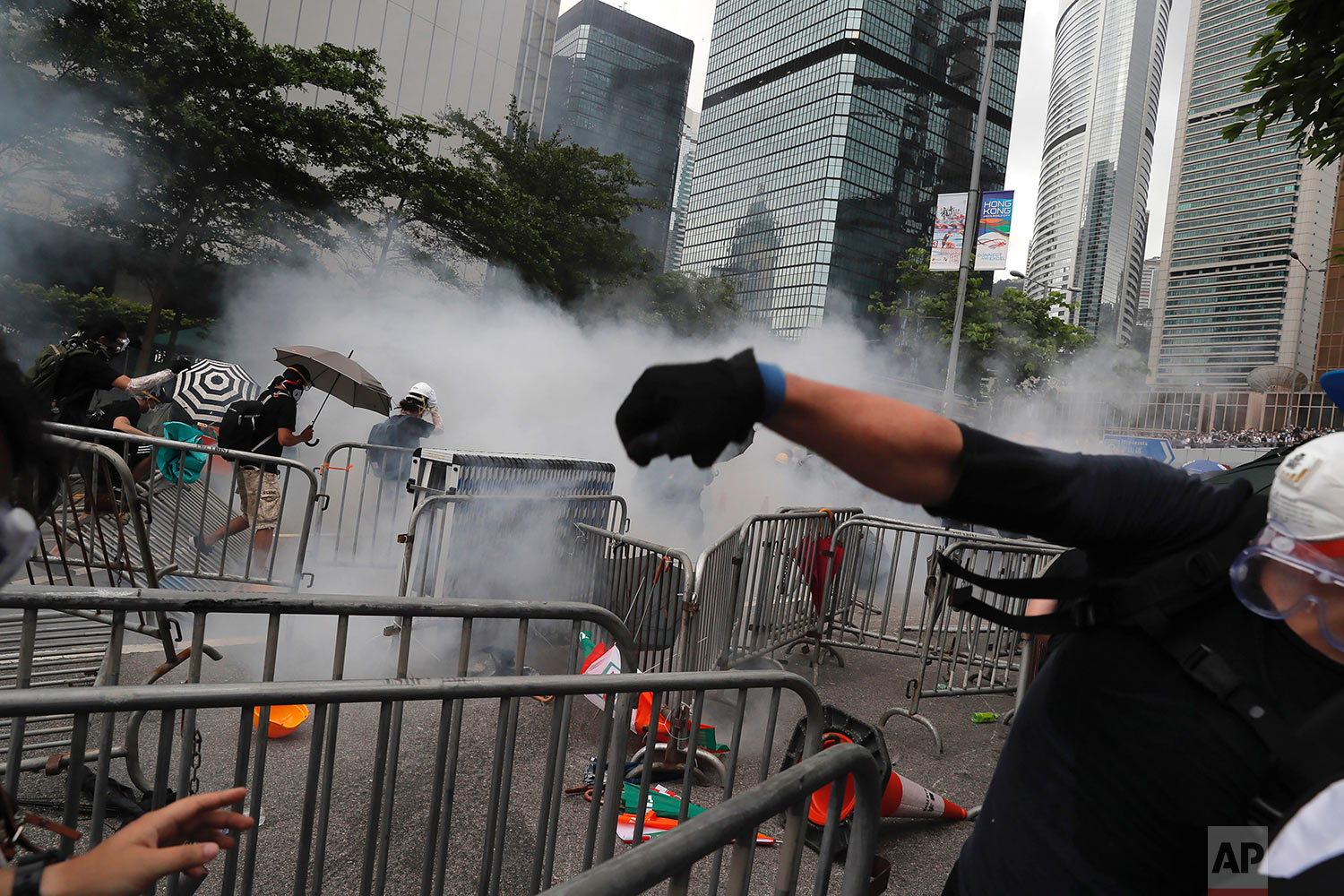 Protesters react to tear gas during a massive protest in Hong Kong, June 12, 2019. (AP Photo/Kin Cheung)