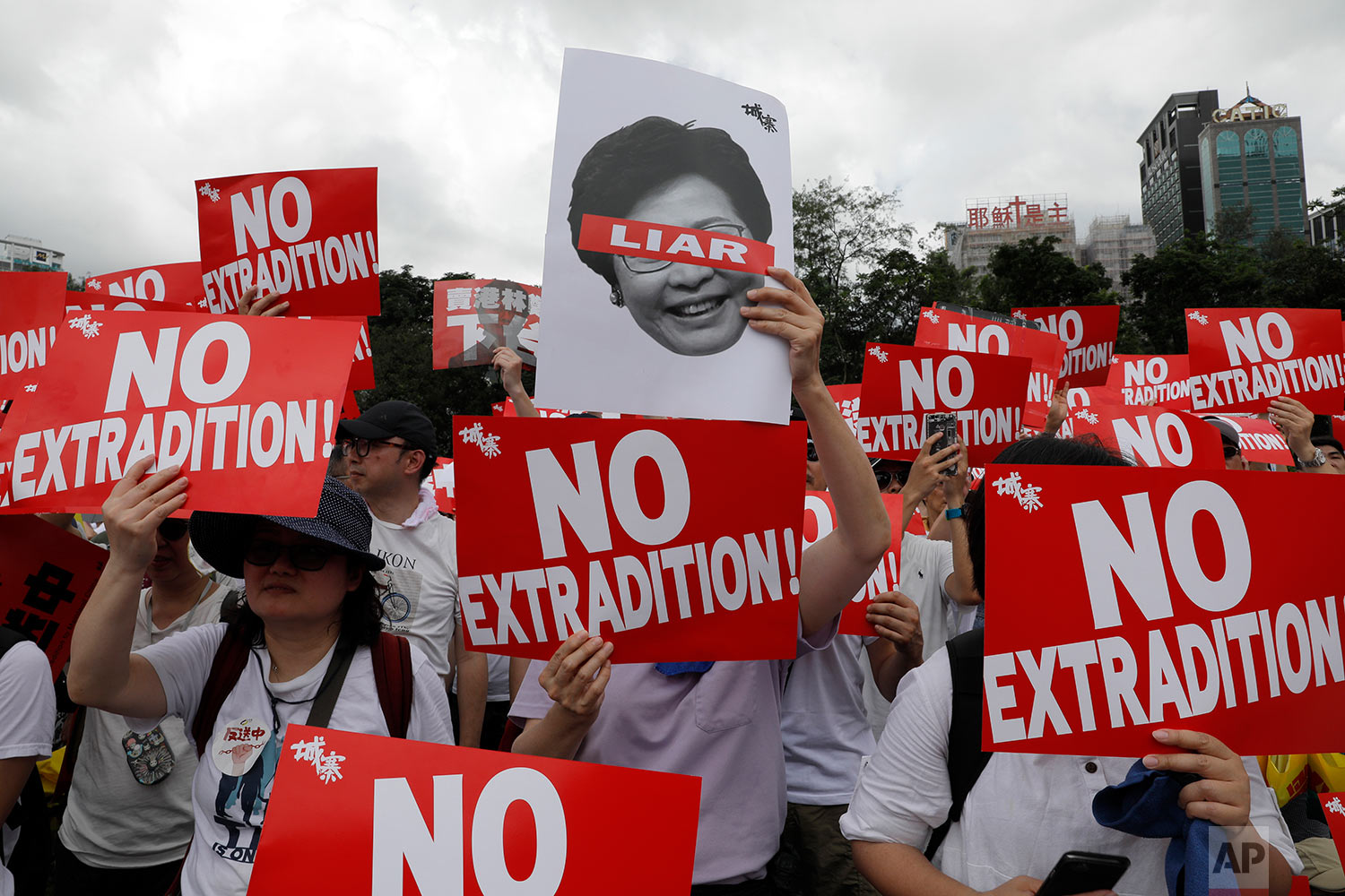 Protesters hold placards as they stage protest against the extradition law in Hong Kong, June 9, 2019. (AP Photo/Vincent Yu)