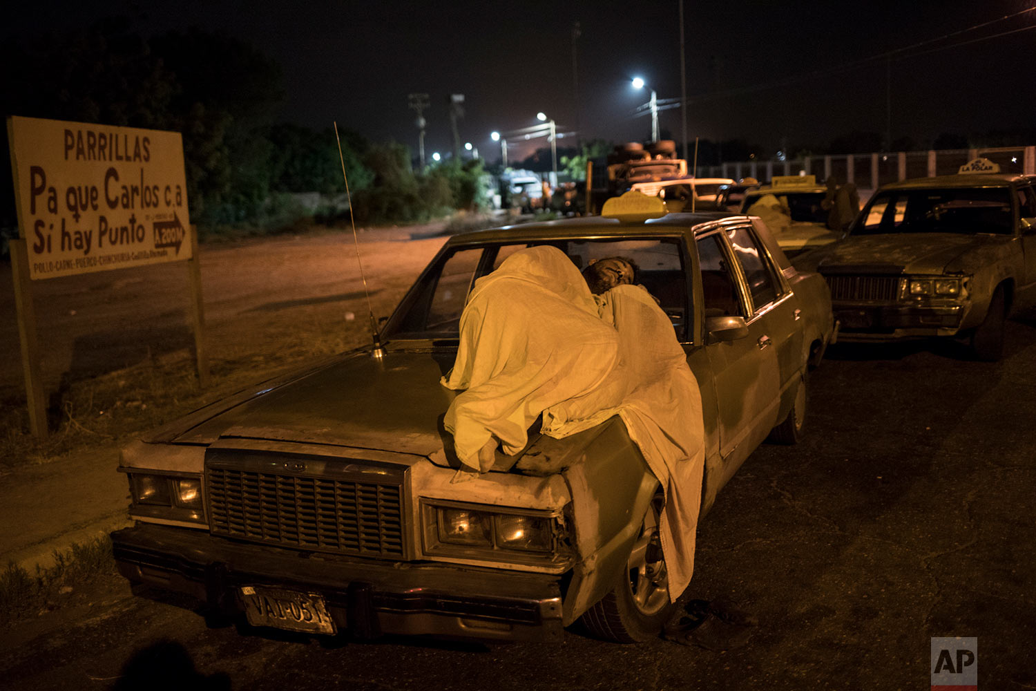 A man sleeps on top of his car as he waits in line to fill up outside a gas station in Maracaibo, Venezuela, May 23, 2019. (AP Photo/Rodrigo Abd)