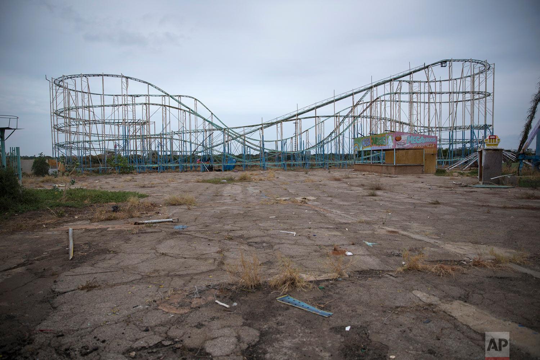 "A roller coaster stands tall in the abandoned amusement park coined ""Diversions Grano de Oro"" in Maracaibo, Venezuela, May 23, 2019. (AP Photo/Rodrigo Abd)"
