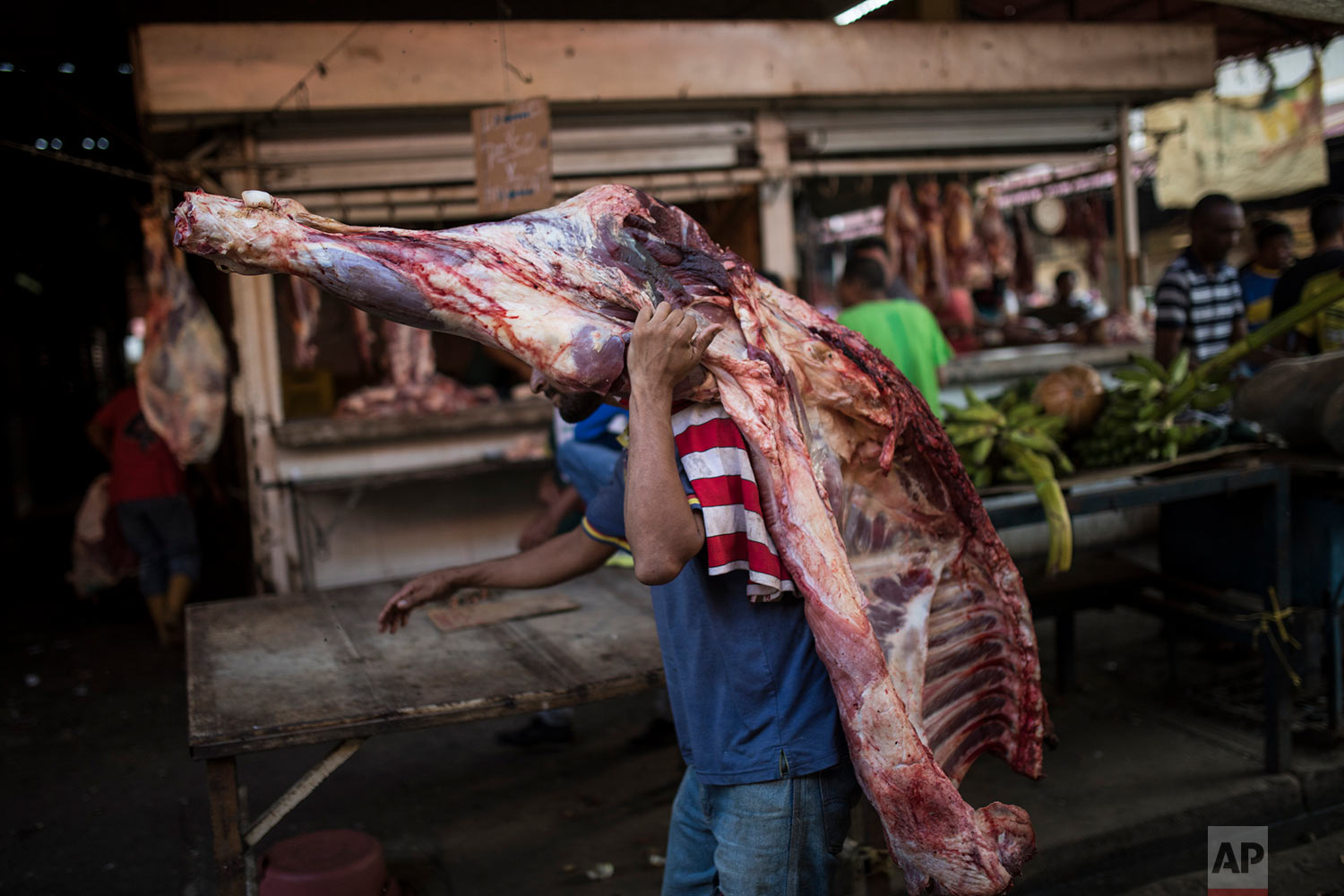 A vendor carries beef to a butcher shop at the flea market in Maracaibo, Venezuela, May 16, 2019. He'll have to sell it quickly, since perishables go bad quickly without refrigeration in Maracaibo's suffocating temperatures. (AP Photo/Rodrigo Abd)