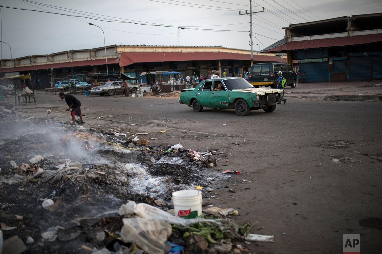 A man searches the trash outside a flea market in Maracaibo, Venezuela, May 14, 2019. (AP Photo/Rodrigo Abd)