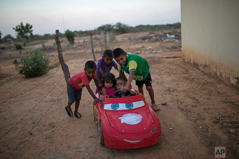 Children play with their toy car in Villa Esperanza neighborhood on the outskirts of Maracaibo, Venezuela, May 15, 2019. (AP Photo/Rodrigo Abd)