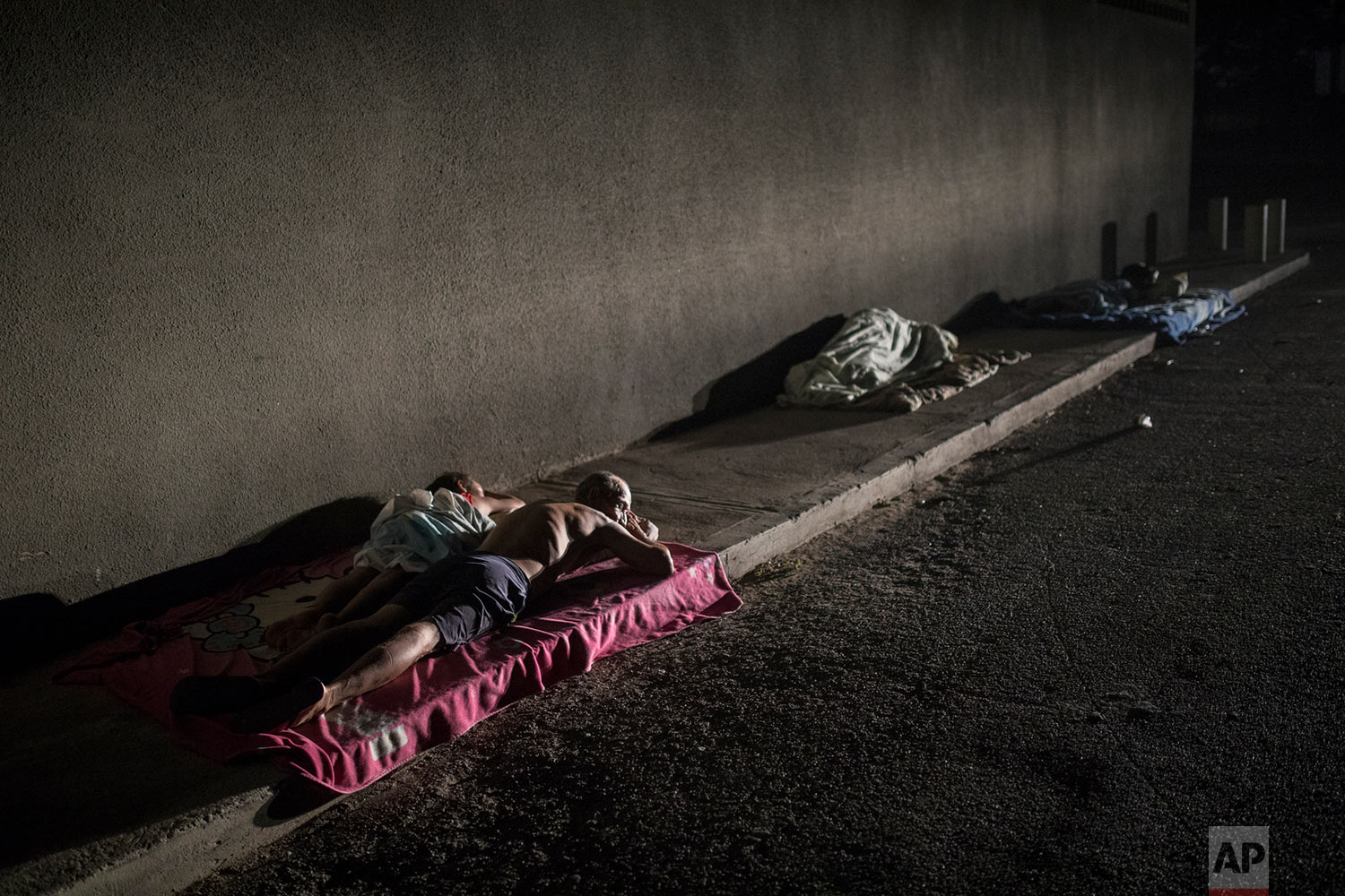People sleep outside their homes for fresh air while air conditioning is not working during a blackout in the sweltering city of Maracaibo, Venezuela, May 15, 2019. (AP Photo/Rodrigo Abd)