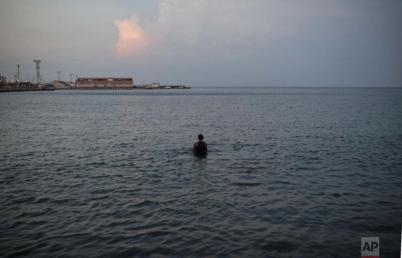 In this May 14, 2019 photo, Raul Navas, 25, bathes in Maracaibo Lake after a day of work a the flea market in Maracaibo, Venezuela. (AP Photo/Rodrigo Abd)