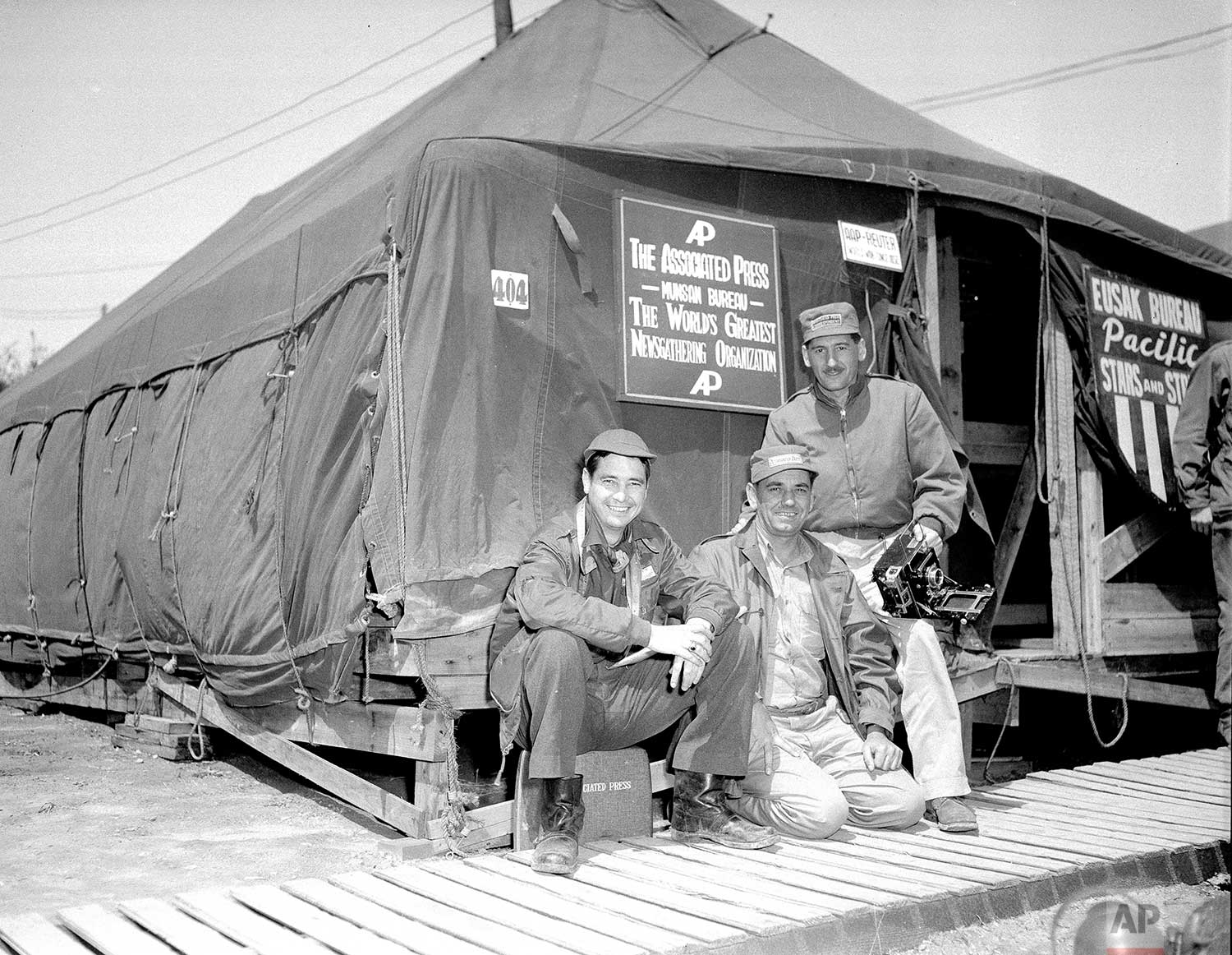 """From left, AP staffers George McArthur, Bill Waugh and Max Desfor sit together outside the new AP press tent at Munsan, Korea, after moving from the train which had been """"home"""" to correspondents since the start of the truce talks. The sign says: The Associated Press, Munsan Bureau, The World's Greatest Newsgathering Organization. (AP Photo)"""