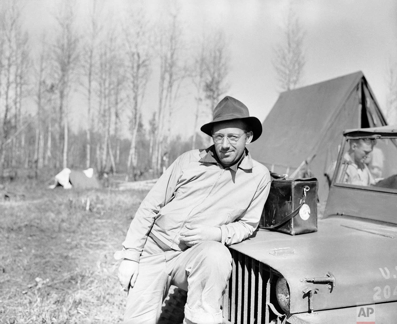Grant MacDonald, Wide World photographer, unshaven, very dirty, and slightly unhappy about it all, rests in the dust and mosquitoes, after reaching the end of the line, last outpost of construction crews on the Alaska road between Fort St. John and Fort Nelson, June 6, 1942. (AP Photo)