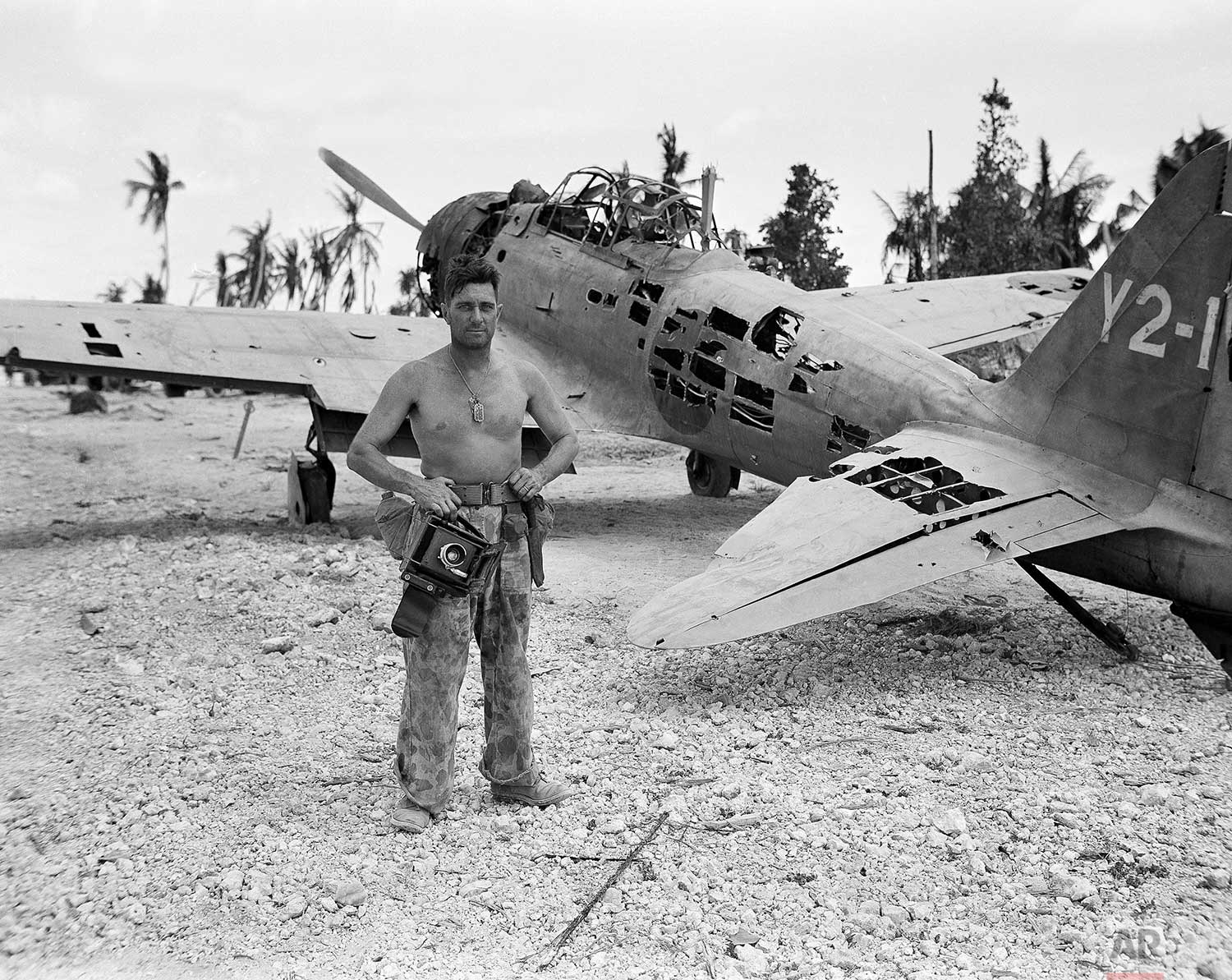 Frank Filan, Associated Press photographer on assignment with wartime still photographer pool, who did his shooting in the American invasion of Tarawa in the Gilberts with a borrowed camera after his camera was lost going ashore with the first Marine wave on November 21, stands near a bullet-riddled plane on the airfield at Tarawa, Dec. 6, 1943. (AP Photo/Frank Filan)