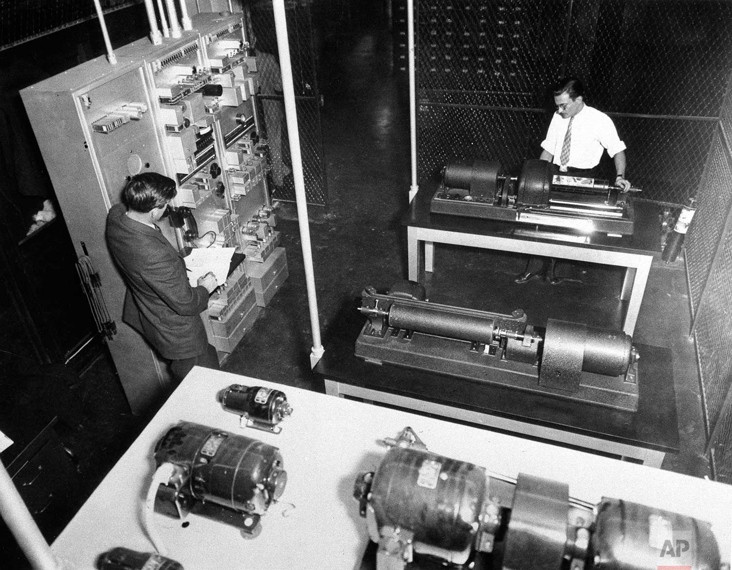 A wire photo receiver showing the cylinder in which the negative is contained, is shown in The Associated Press' photo department in New York, 1935, with Eddie Nittoly, right, attending to the machine. (AP Photo)