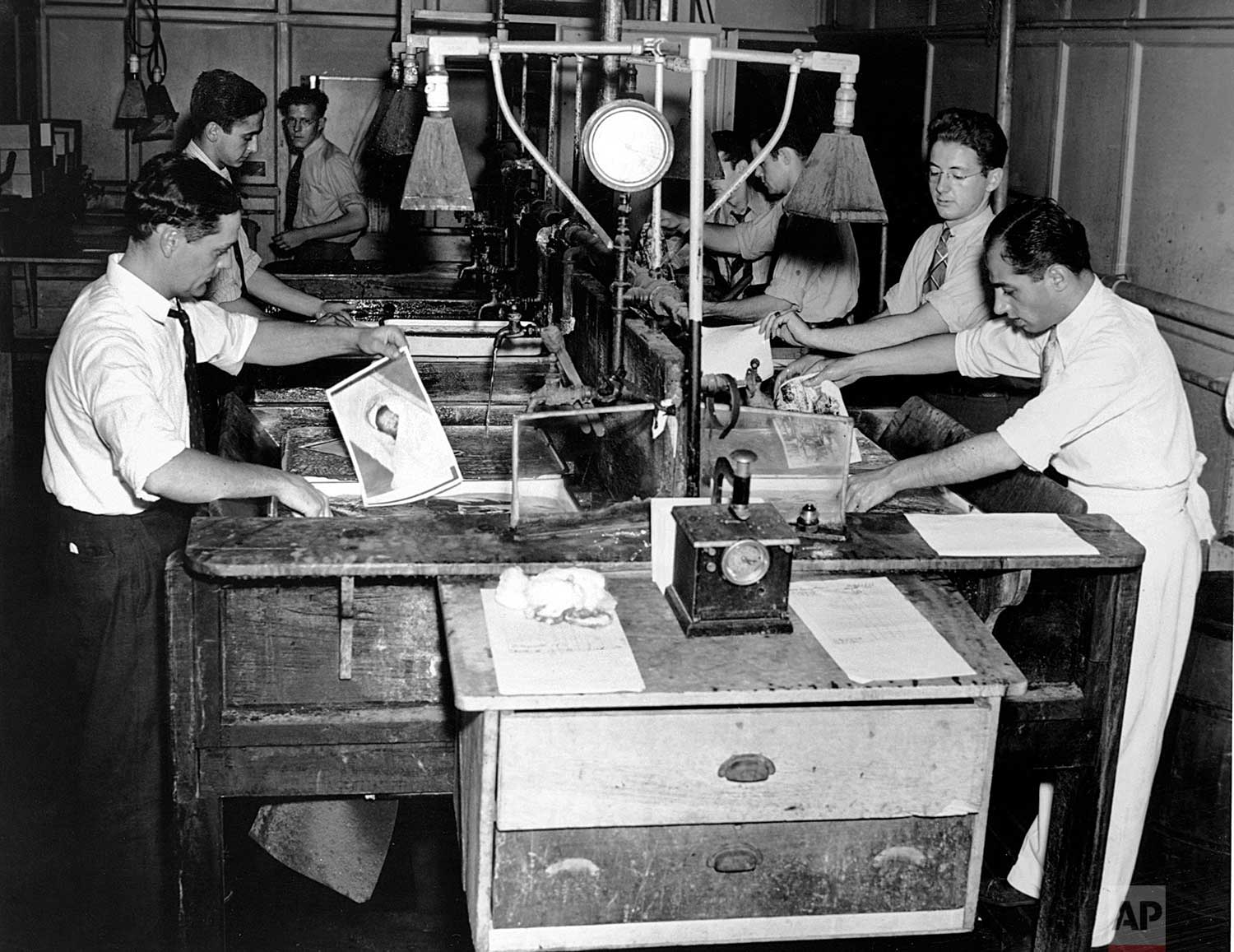 Marty Lederhandler, second from right, works in the darkroom of AP's New York headquarters on Madison Ave. ca. 1936. Lederhandler, who became an AP photographer, captured on film every U.S. president from Herbert Hoover to Bill Clinton, covered the D-Day landing in 1944 and climaxed a 66-year career with an iconic shot of the 9/ll World Trade Center attacks. (AP Photo/Corporate Archives)