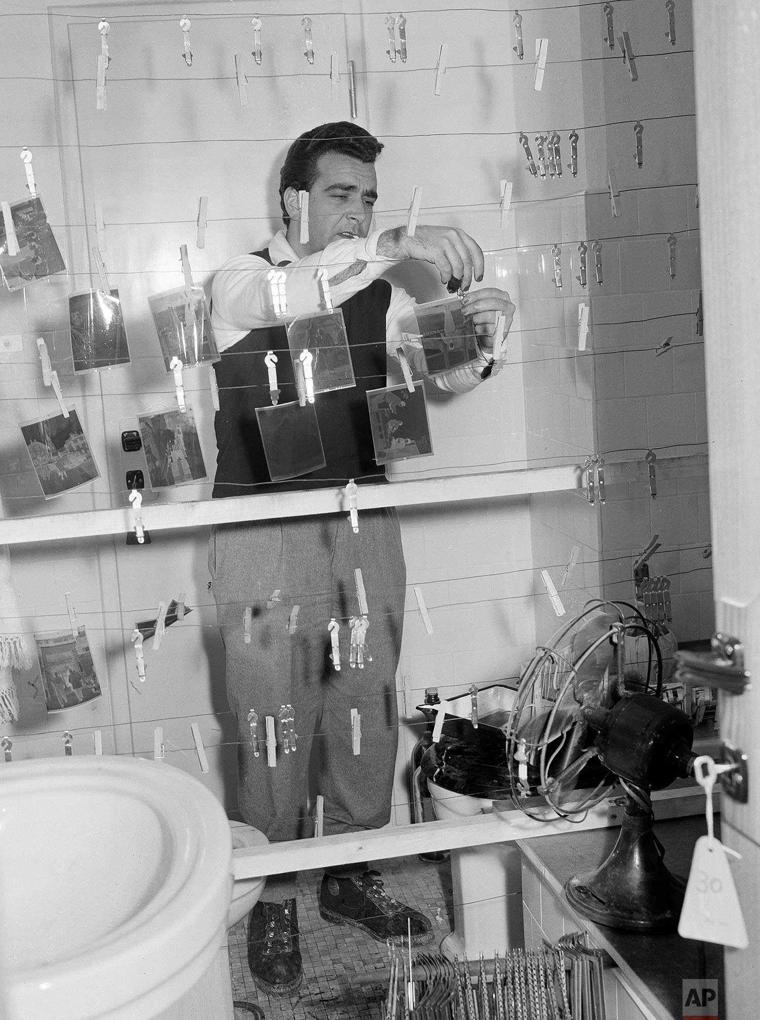 Rome darkroom staffer Carlo Pelliccia dries negatives in a bathroom where film for five AP photographers was being processed during the 1956 Winter Olympics in Cortina, Italy. (AP Photo/Walter Attenni)
