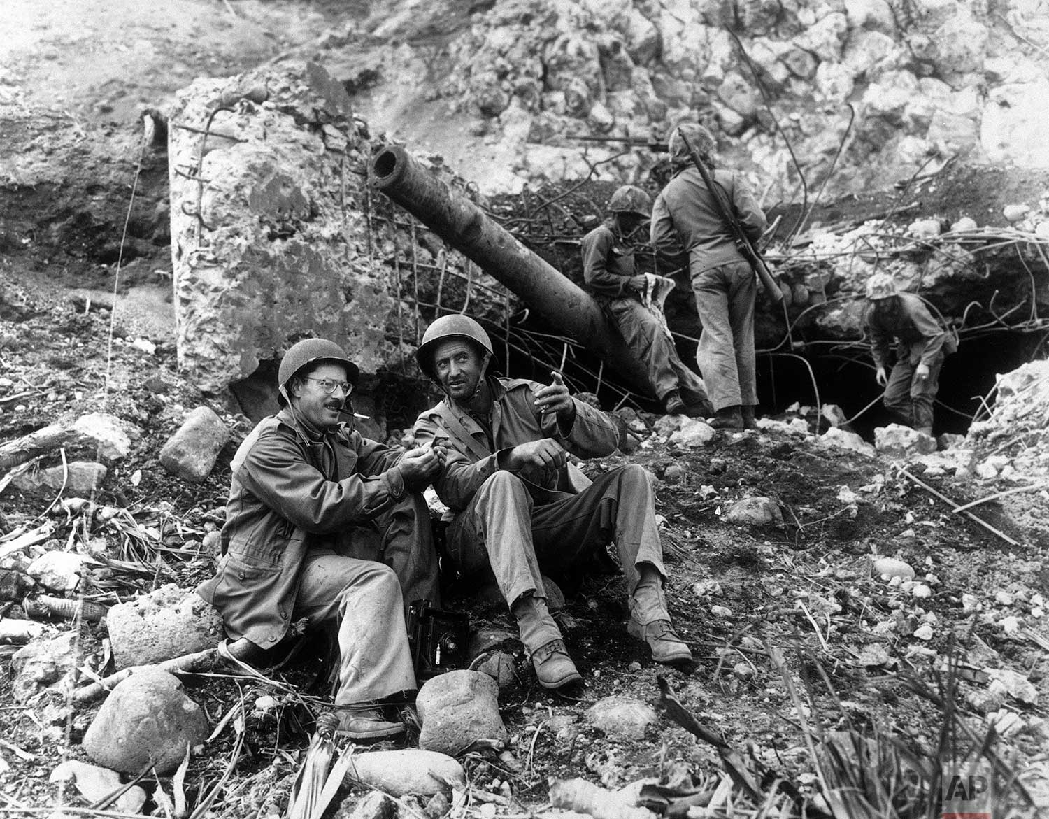 Associated Press photographer with the wartime pool, Joe Rosenthal, takes time out to rest with Bob Campbell, a Marine from San Francisco, March 2, 1945, in front of a large Japanese gun knocked out by Marines at the base of Mount Suribachi. Rosenthal scaled the mountain to make the picture of the U.S. flag being raised there. (AP Photo)