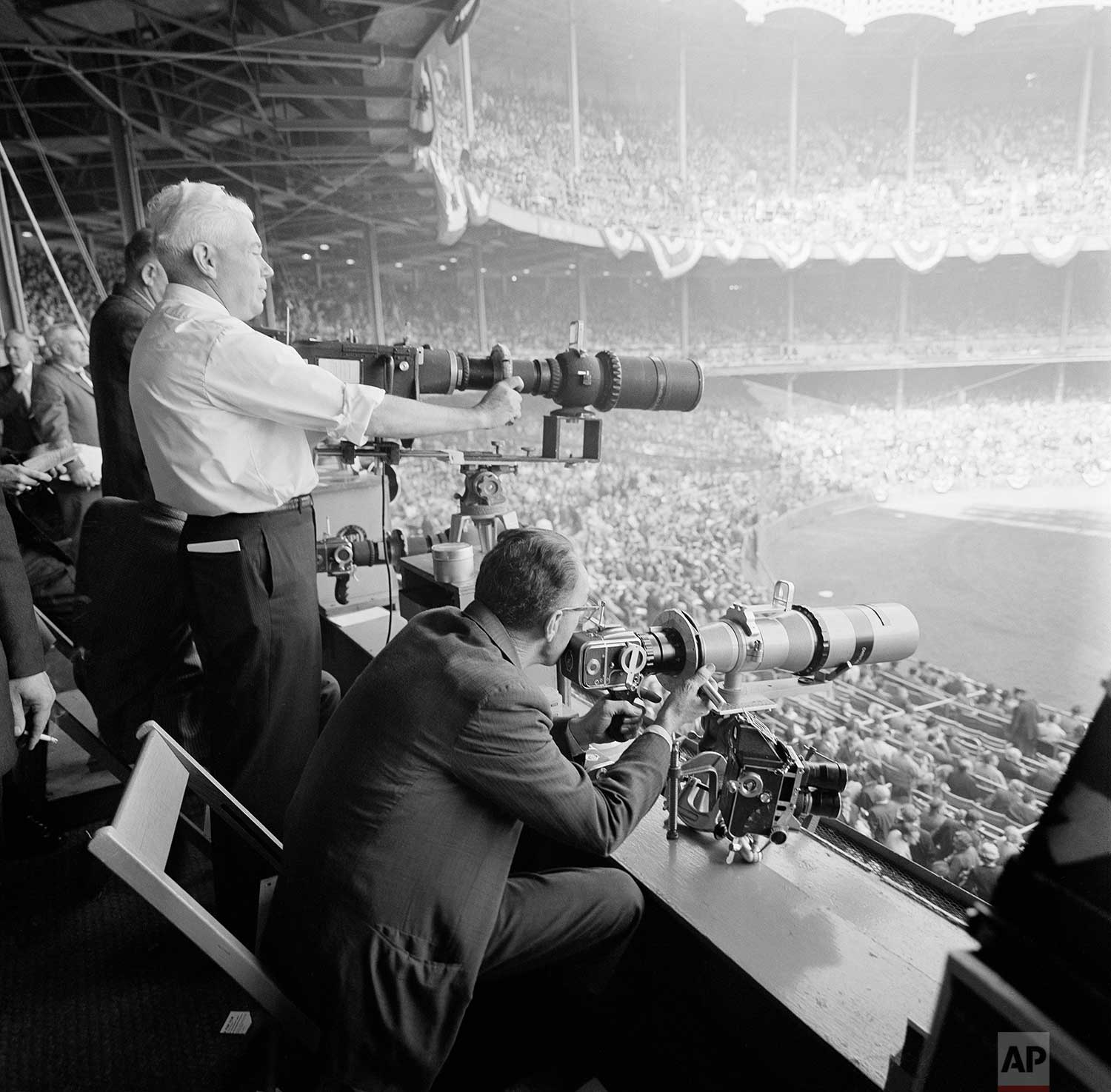 Photographers of The Associated Press are pictured at work in Yankee Stadium in New York, covering the second game of the 1961 World Series between the New York Yankees and the Cincinnati Reds, Oct. 5, 1961. From foreground to background are Harry Harris, John Rooney and Murray Becker. (AP Photo)