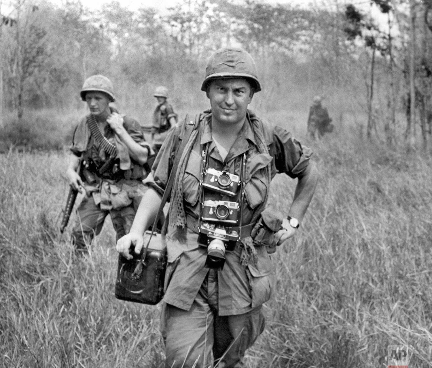Associated Press photographer Horst Faas, with his Leica cameras around his neck, accompanies U.S. troops in War Zone C in Vietnam, 1967. (AP Photo/Courtesy of Horst Faas)