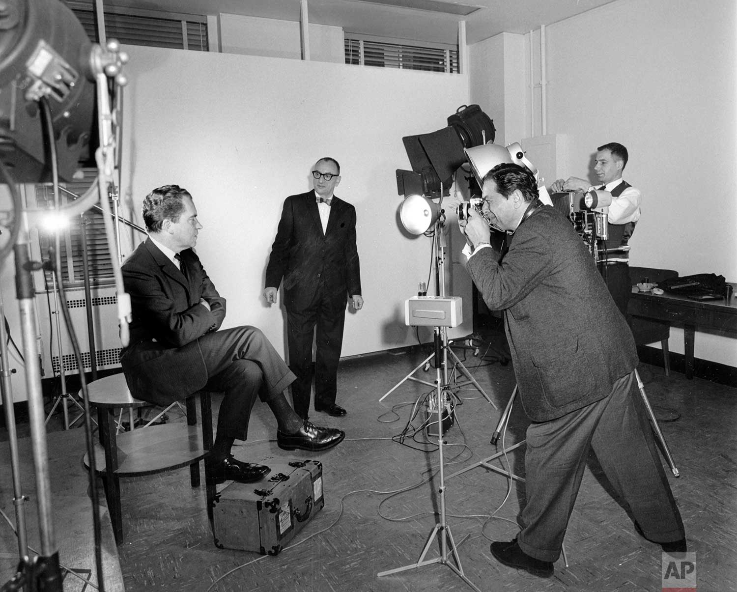 Former Vice President Richard Nixon, left, sits for a portrait at Associated Press headquarters in New York on his 51st birthday, Jan. 9, 1964. AP chief photographer Murray Becker, center, directs the shoot with photographers Tony Camerano, foreground, and Ed (Eddie) Adams, right. (AP Photo/Corporate Archives)