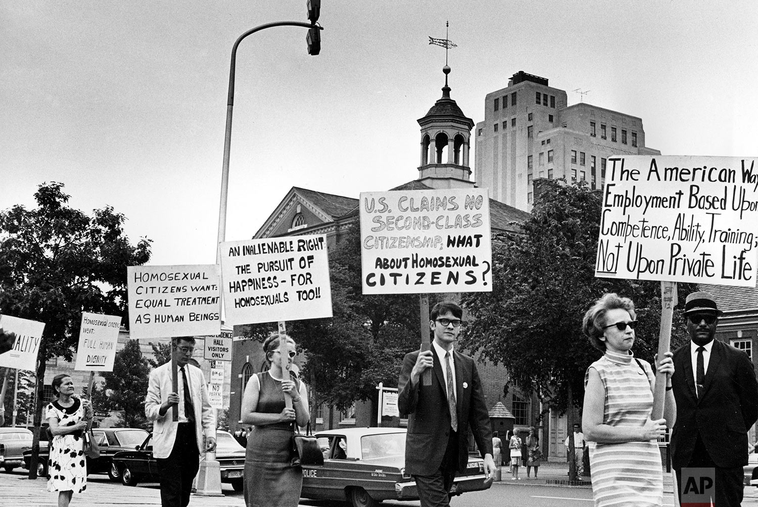 In this July 4, 1967 file photo Kay Tobin Lahusen, right, and other demonstrators carry signs calling for protection of homosexuals from discrimination as they march in a picket line in front of Independence Hall in Philadelphia. In 2019, same-sex marriage is the law of the land in the U.S. and at least 25 other countries. LGBT Americans serve as governors, big-city mayors and members of Congress, and one _ Pete Buttigieg _ is waging a spirited campaign for president. (AP Photo/John F. Urwiller)