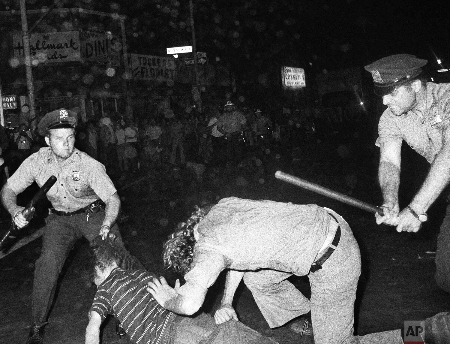 In this Aug. 31, 1970 file photo, an NYPD officer grabs a youth by the hair as another officer clubs a young man during a confrontation in Greenwich Village after a Gay Power march in New York. A year earlier, the June 1969 uprising by young gays, lesbians and transgender people in New York City, clashing with police near a bar called the Stonewall Inn, was a vital catalyst in expanding LGBT activism nationwide and abroad. (AP Photo)