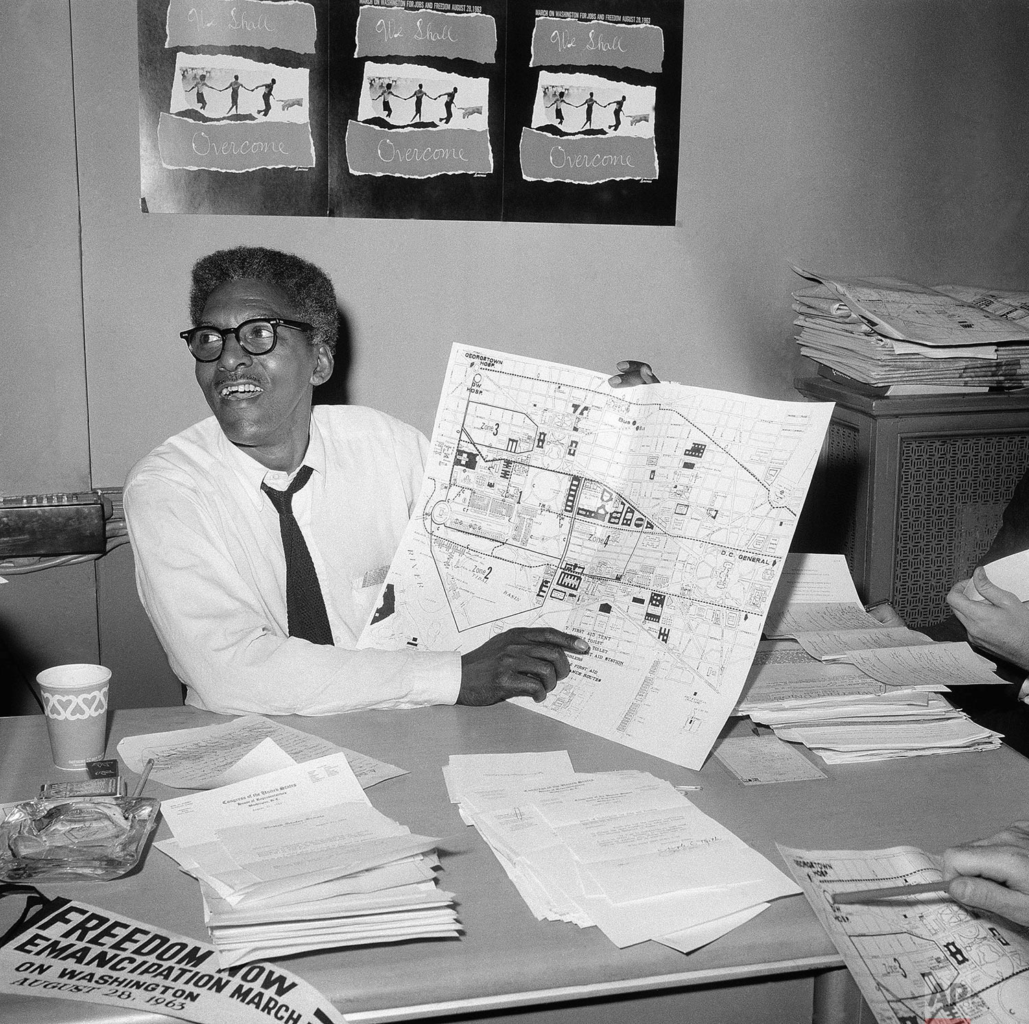 """In this Aug. 24, 1963 file photo, Bayard Rustin points to a map showing the path of the March on Washington during a news conference at the New York City headquarters. Months before Martin Luther King Jr.'s """"I Have a Dream"""" declaration galvanized a quarter-million people at the 1963 March on Washington, Rustin was planning all the essential details to keep the crowd orderly and engaged. A Quaker and a pacifist, Rustin served as chief strategist for King's march over the objections of some leaders, but was kept mostly in the background with some organizers considering him a liability. Notably, he was gay in an era when same-sex relations were widely reviled in American society. He died in 1987, and is sometimes forgotten in civil rights history. (AP Photo)"""