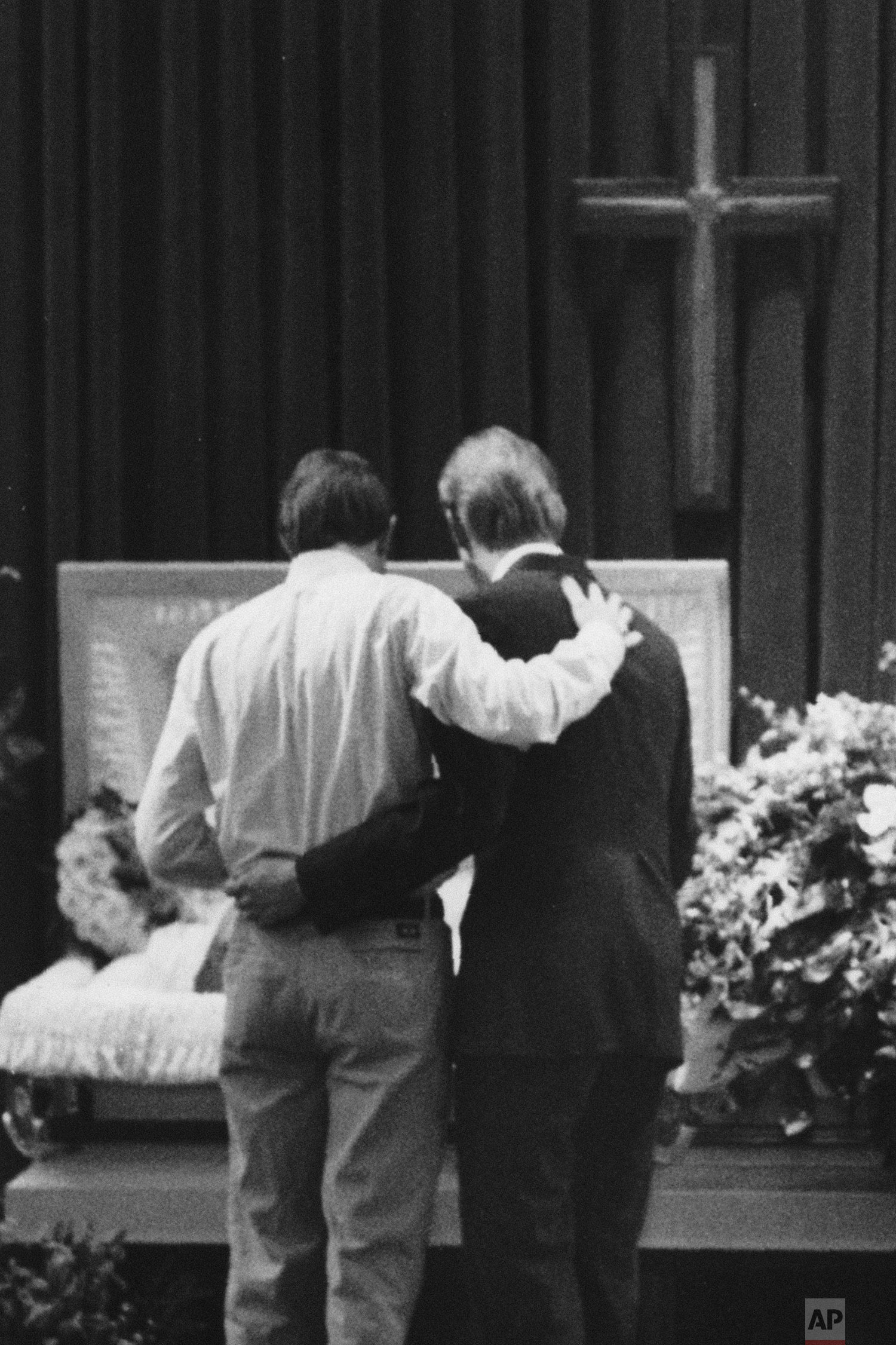 In this March 11, 1991 file photo, mourners embrace each other next to the casket of AIDS patient David Thurmond during his funeral service in Houston. (AP Photo/Houston Chronicle, John Everett)