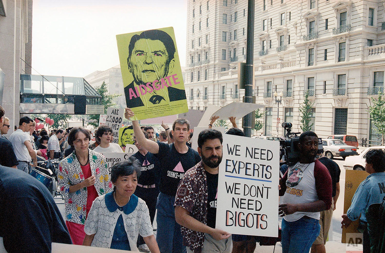 In this Wednesday, Sept. 9, 1987 file photo, protesters carry signs, including one depicting President Ronald Reagan, during a demonstration outside the National Press Club in Washington. The demonstration was held as the president's AIDS commission met at the press club. (AP Photo/Dennis Cook)