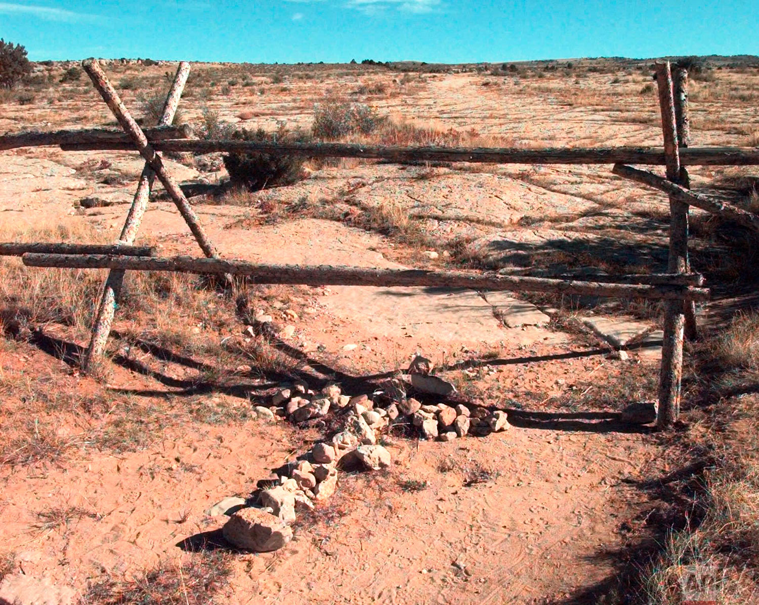In this Oct. 9, 1999 file photo, a cross made of stones rests below the fence in Laramie, Wyo., where a year earlier, University of Wyoming student Matthew Shepard was tied and pistol whipped into a coma. He later died. The murder of Shepard was a watershed moment for gay rights and LGBTQ acceptance in the U.S. (AP Photo/Ed Andrieski)