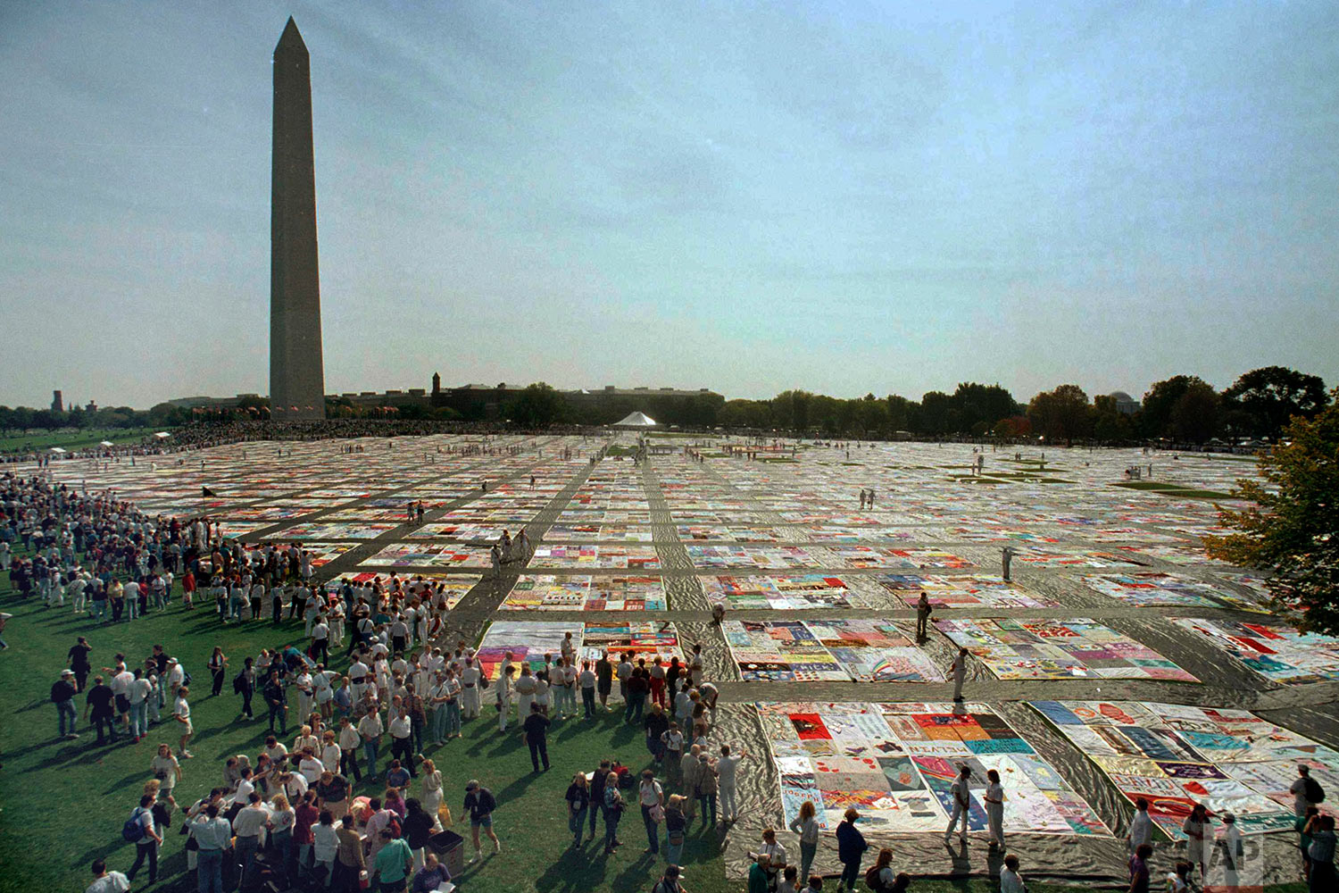 In this Saturday, Oct. 10, 1992 file photo, people visit the 21,000 panel Names Project AIDS Memorial Quilt in Washington. The Washington Monument is seen in the background. (AP Photo/Shayna Brennan)