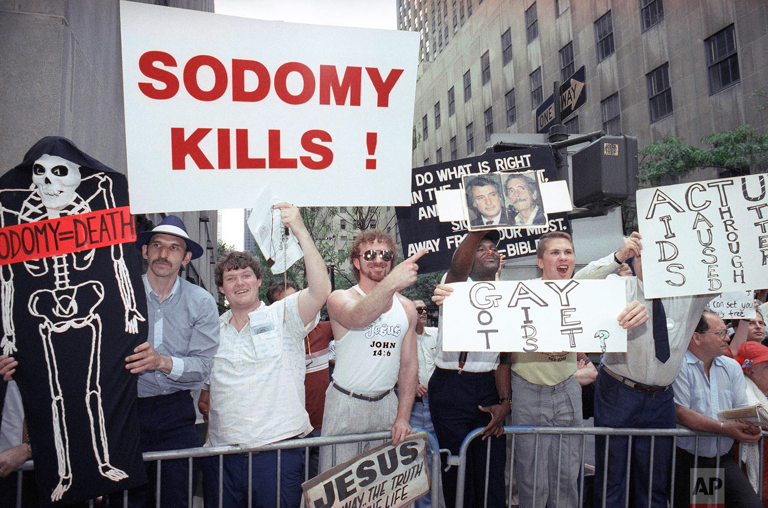 In this Sunday, June 25, 1990 file photo, anti-gay protesters heckle marchers in the Gay Pride Parade along Fifth Avenue in New York. About 200,000 people marched in the 21st annual gay and lesbian parade in Manhattan demanding better AIDS treatment and civil rights. (AP Photo/David A. Cantor)