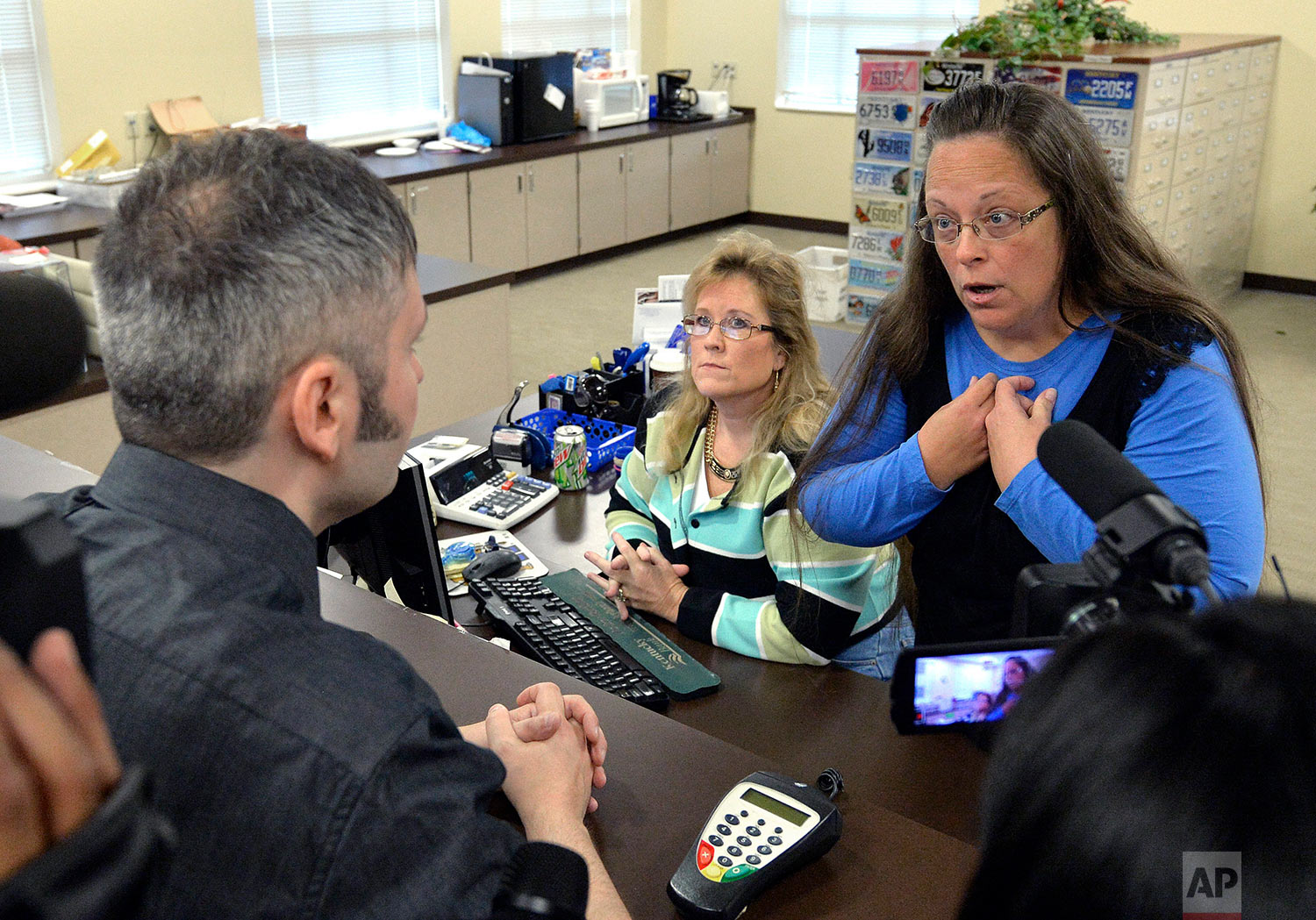 In this Tuesday, Sept. 1, 2015 file photo, Rowan County Clerk Kim Davis, right, talks with David Moore following her office's refusal to issue marriage licenses at the Rowan County Courthouse in Morehead, Ky. Although her appeal to the U.S. Supreme Court was denied, Davis still refuses to issue marriage licenses. (AP Photo/Timothy D. Easley)