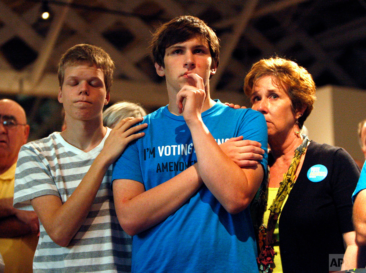 In this Tuesday, May 8, 2012 file photo, Seth Keel, center, is consoled by his boyfriend, Ian Chambers, left, and his mother Jill Hinton, during a concession speech at an Amendment One opposition party in downtown Raleigh, N.C. North Carolina voters approved the constitutional amendment Tuesday defining marriage solely as a union between a man and a woman, becoming the latest state to effectively stop same-sex marriages. (Travis Long/The News & Observer via AP)
