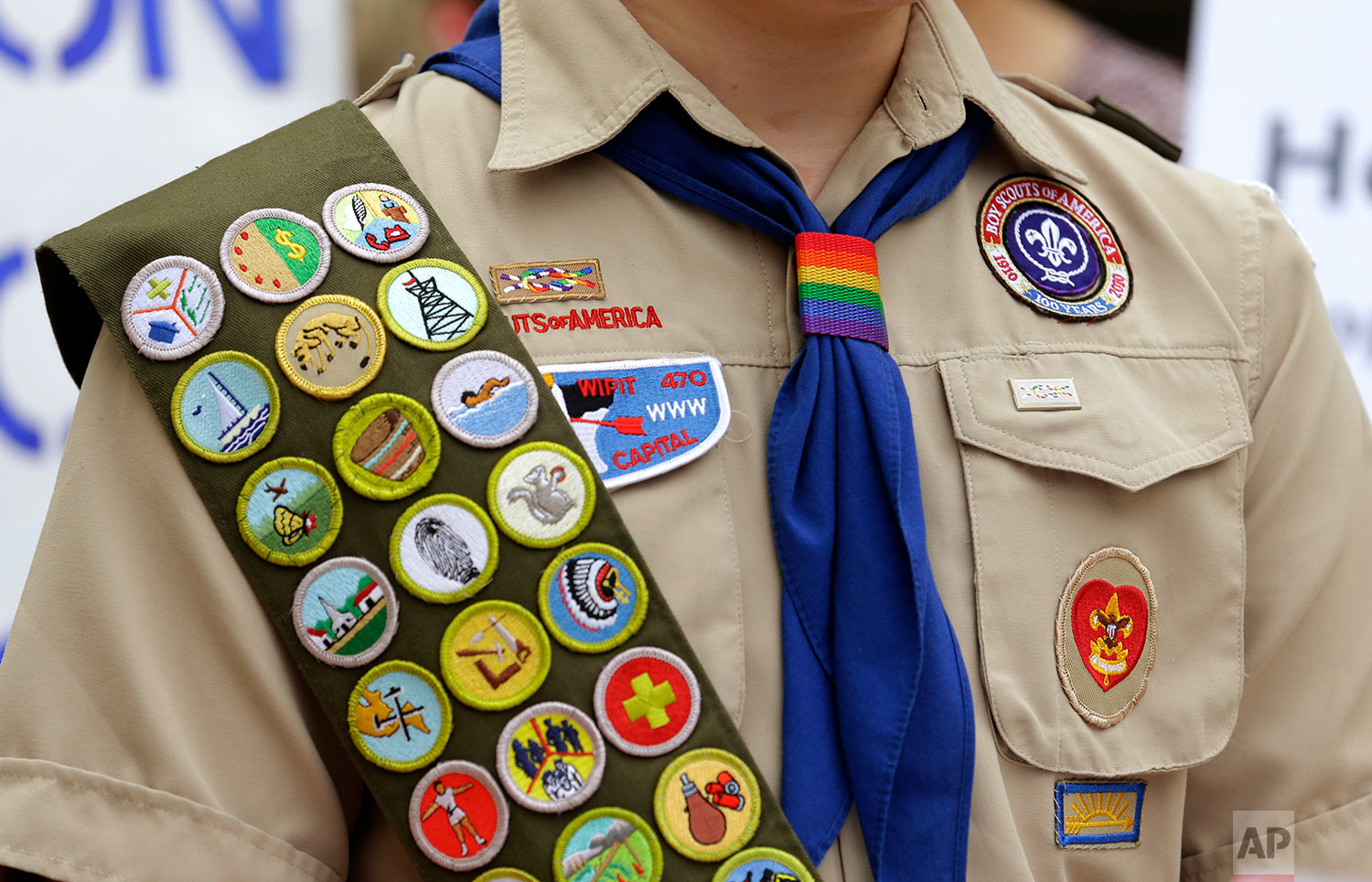 This Wednesday, May 21, 2014 file photo shows merit badges and a rainbow-colored neckerchief slider on the Boy Scout uniform of Pascal Tessier, 17, a gay Eagle Scout from Kensington, Md., as he speaks in front of a group of scouts and scout leaders, outside the headquarters of Amazon in Seattle. The group delivered a petition to Amazon that was started as an online effort by Tessier, urging Amazon to stop donating money to the Boy Scouts due to the organization's policy of excluding openly gay adults from leadership positions, despite recently accepting gay youth as scouts. (AP Photo/Ted S. Warren)