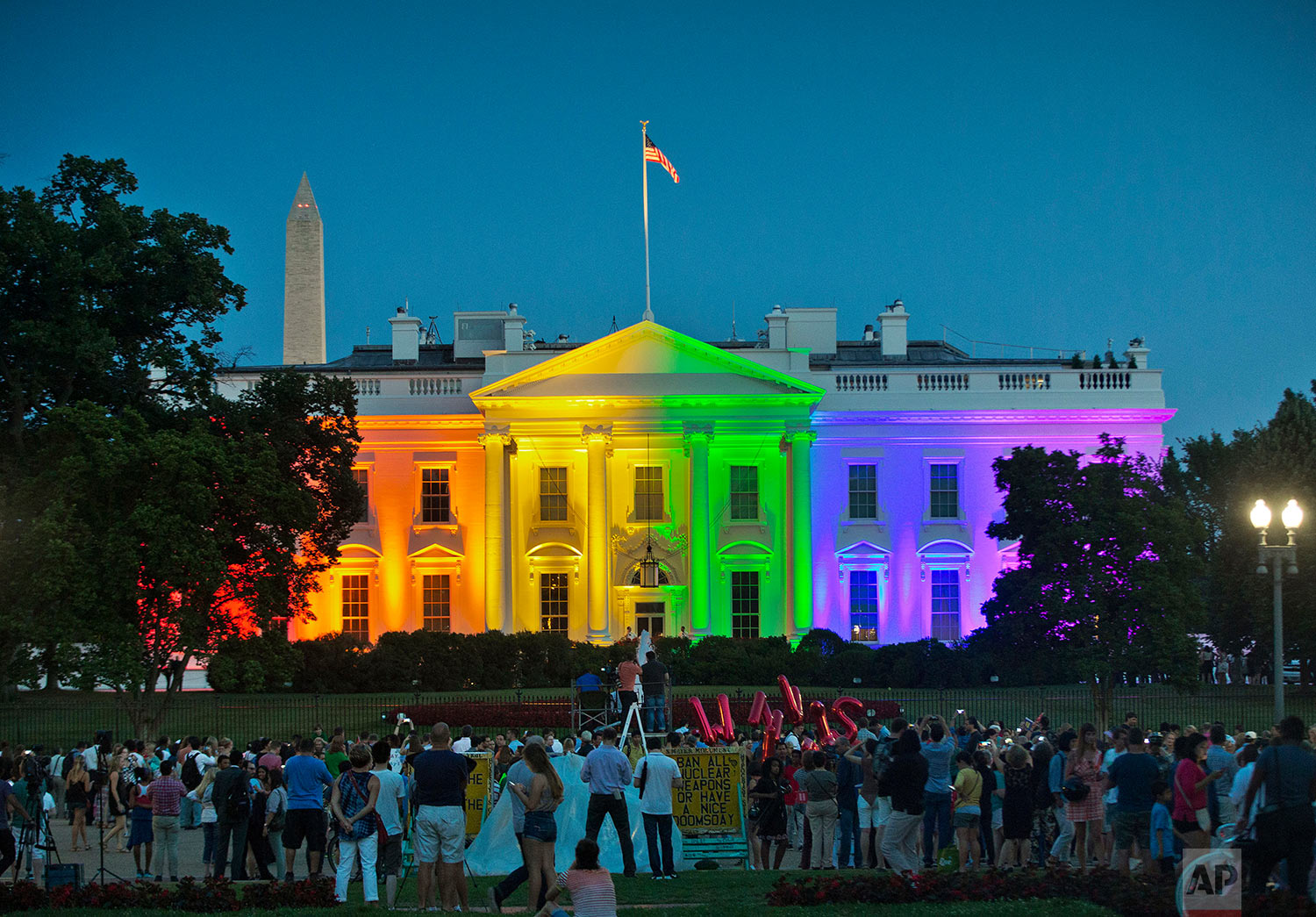 """In this Friday, June 26, 2015 file photo, people gather in Lafayette Park to see the White House illuminated with rainbow colors in commemoration of the Supreme Court's ruling to legalize same-sex marriage in Washington. President Barack Obama, who was inside, said a few days later, """"To see people gathered in the evening outside on a beautiful summer night, and to feel whole and to feel accepted, and to feel that they had a right to love _ that was pretty cool."""" (AP Photo/Pablo Martinez Monsivais,)"""