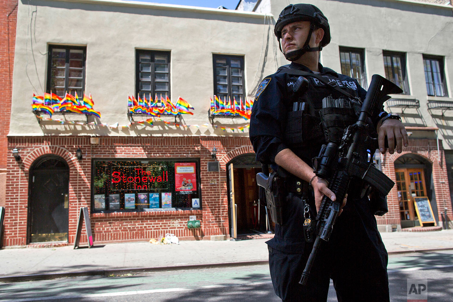 In this June 12, 2016 file photo, an armed police officer stands guard outside the Stonewall Inn in New York, after a gunman in Orlando, Fla., opened fire in a gay nightclub, spreading fear of more attacks. (AP Photo/Mary Altaffer)