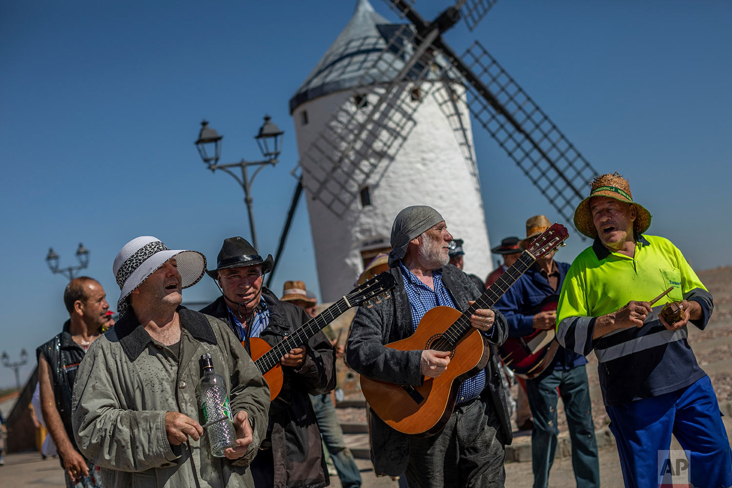 "In this Friday, June 21, 2019 photo, members of the ""Hermandad del santísimo sacramento pecados y danzantes"" brotherhood sing satirical songs during a procession as part of Corpus Christi celebrations in Camunas, central Spain. (AP Photo/Bernat Armangue)"