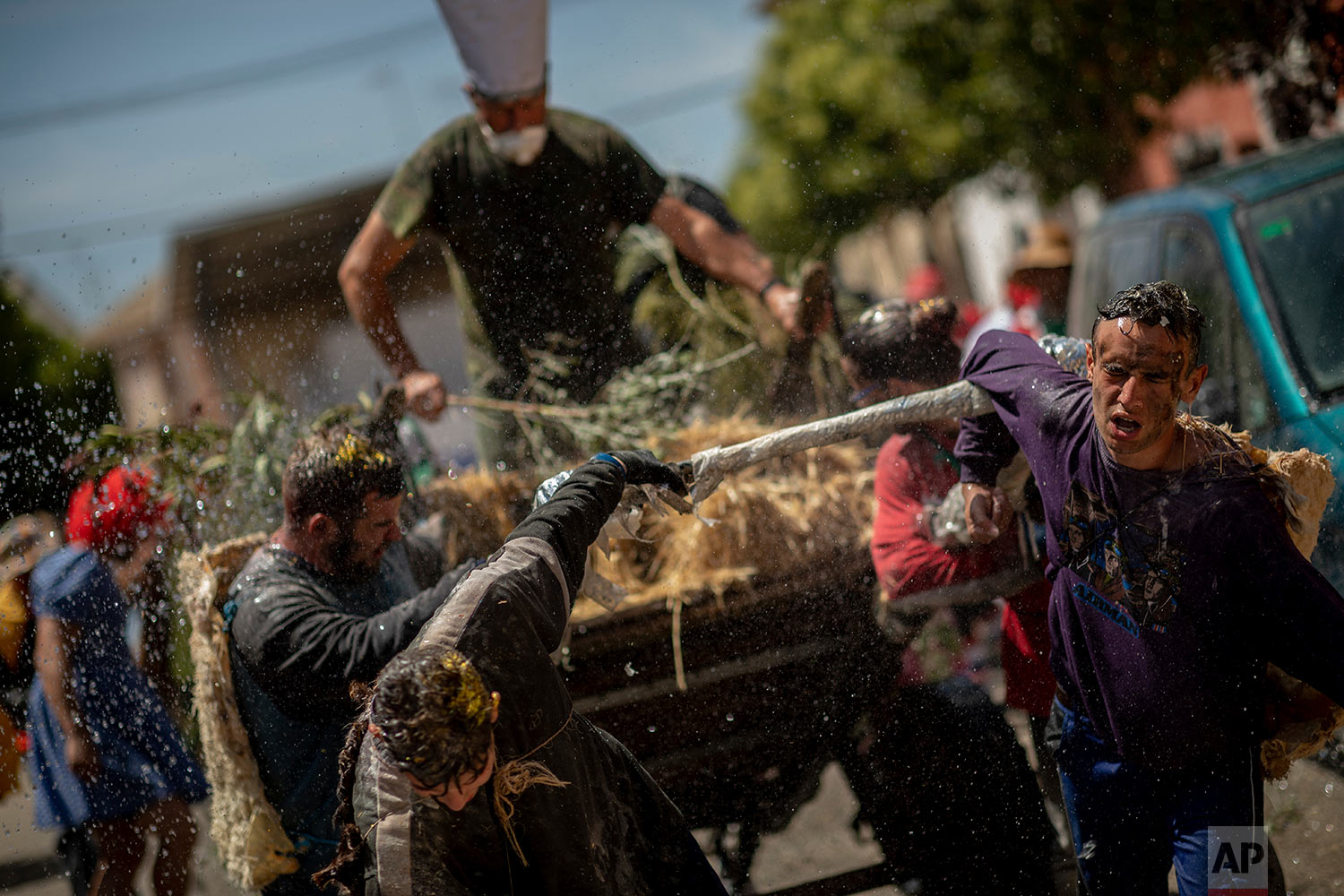 "In this Friday, June 21, 2019 photo, novice members of the ""Hermandad del santísimo sacramento pecados y danzantes"" brotherhood pull a cart during a procession as part of Corpus Christi celebrations in Camunas, central Spain.  (AP Photo/Bernat Armangue)"