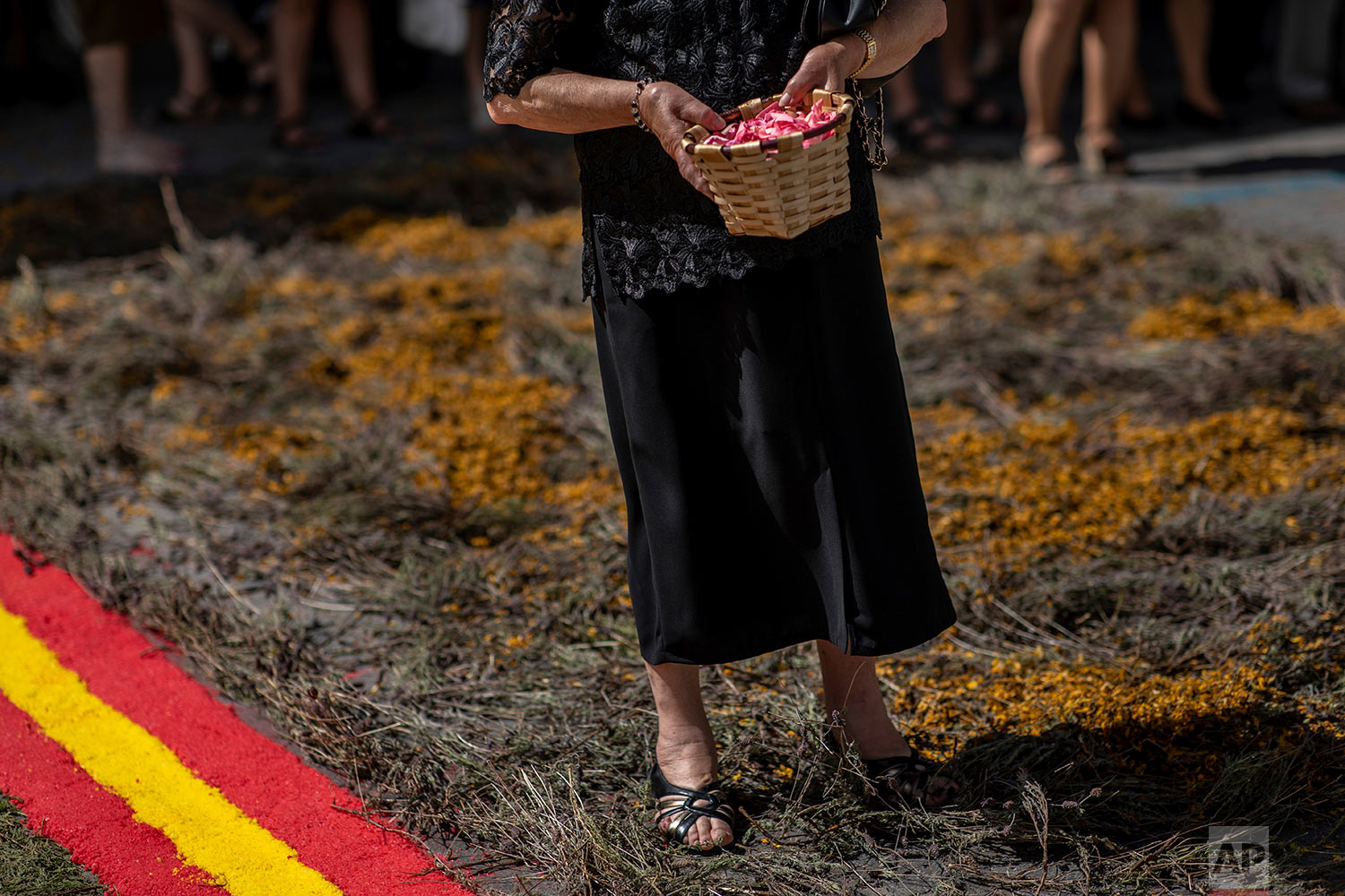 A Catholic worshipper holds a basket with rose petals during the Corpus Christi procession in the village of Bejar, Spain, Sunday, June 23, 2019. (AP Photo/Bernat Armangue)