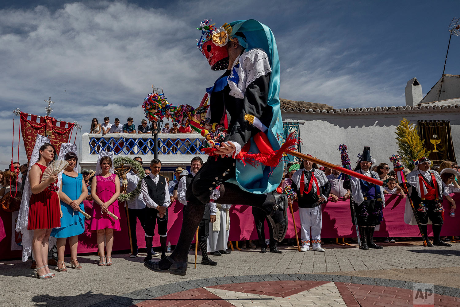 "In this Thursday, June 20, 2019 photo, a member of the ""Hermandad del santísimo sacramento pecados y danzantes"" brotherhood representing the sins jumps during a Corpus Christi procession in Camunas, central Spain. (AP Photo/Bernat Armangue)"