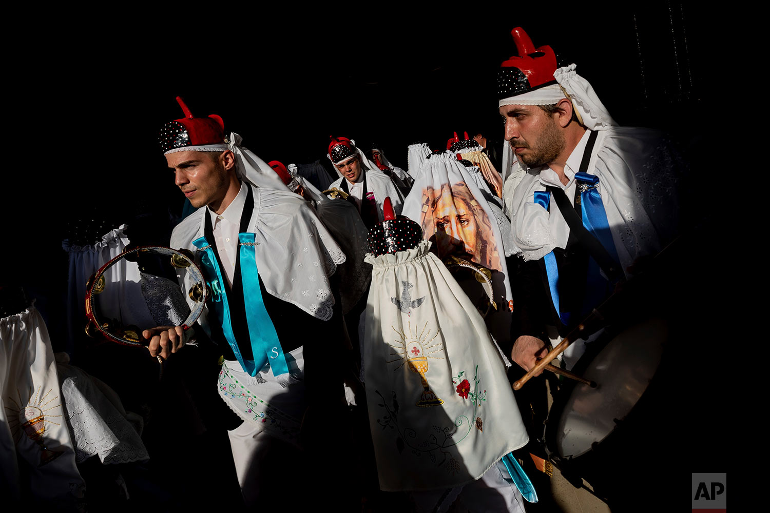 "In this Thursday, June 20, 2019 photo, members of the ""Hermandad del santísimo sacramento pecados y danzantes"" brotherhood representing the goodness take part in a Corpus Christi procession in Camunas, central Spain. (AP Photo/Bernat Armangue)"