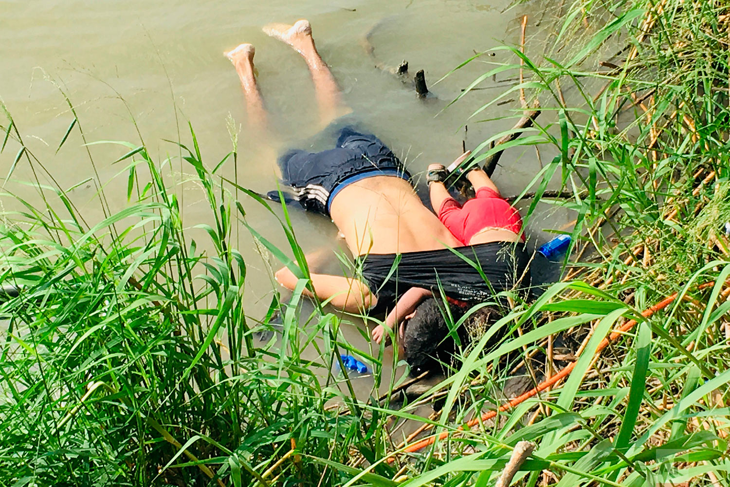 The bodies of Salvadoran migrant Oscar Alberto Martínez Ramírez and his nearly 2-year-old daughter Valeria lie on the bank of the Rio Grande in Matamoros, Mexico, Monday, June 24, 2019, after they drowned trying to cross the river to Brownsville, Texas. (AP Photo/Julia Le Duc)