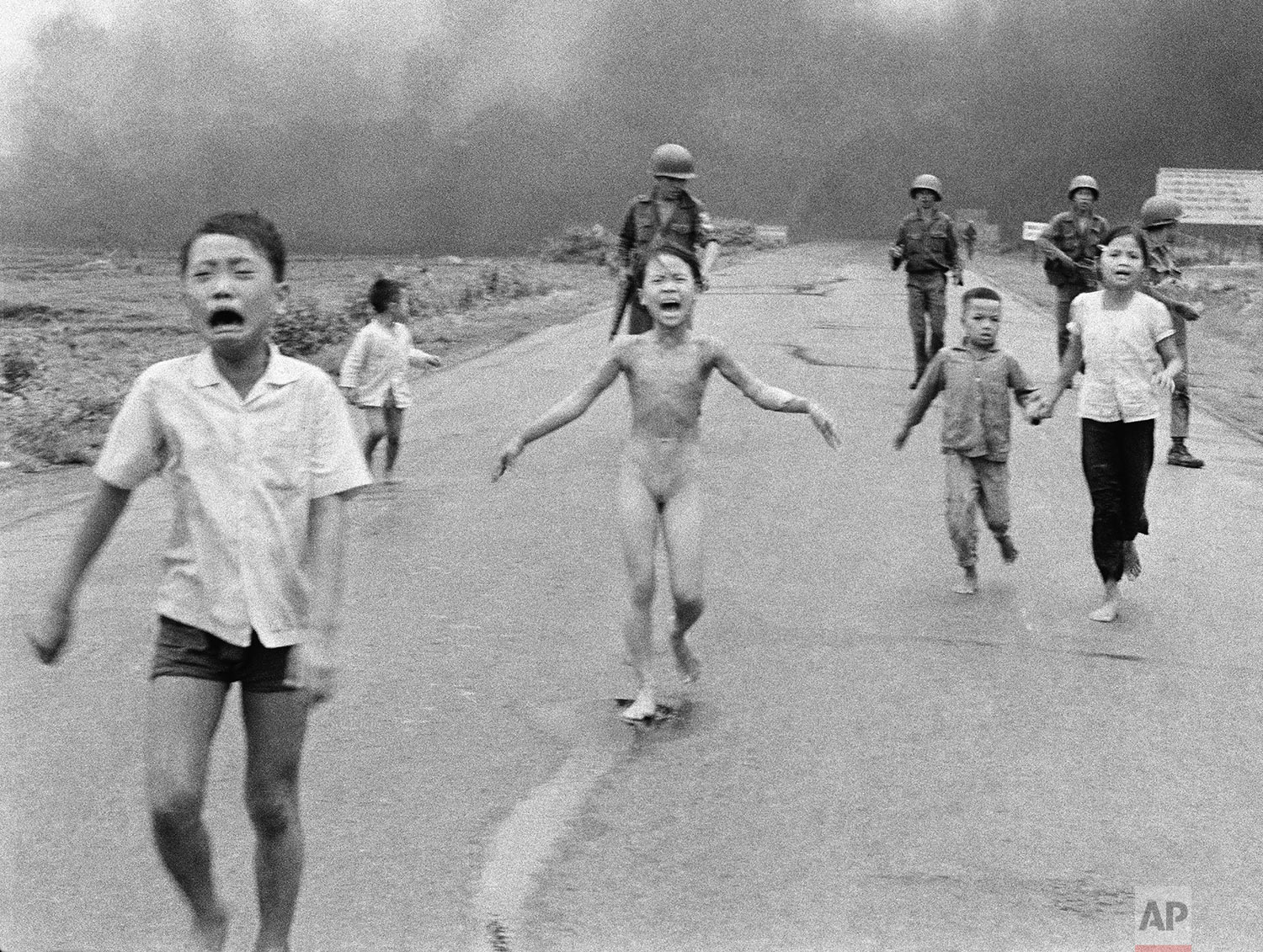 South Vietnamese forces follow after terrified children, including 9-year-old Kim Phuc, center, as they run down Route 1 near Trang Bang after an aerial napalm attack on suspected Viet Cong hiding places on June 8, 1972. (AP Photo/Nick Ut)