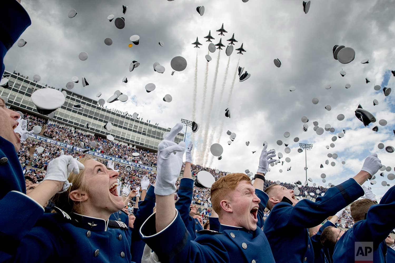 United States Air Force Academy cadets toss their hats in the air as the Thunderbirds fly overhead during the cadets' graduation ceremony at Falcon Stadium., Thursday, May 30, 2019, in Colorado Springs, Colo. (AP Photo/Andrew Harnik)