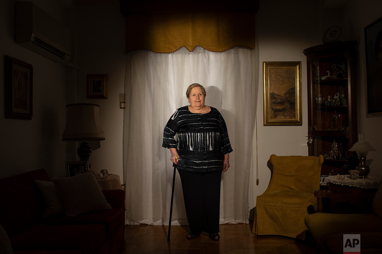 Christina Samada, a 75-year-old pensioner, poses for a photo in her house in Athens. (AP Photo/Petros Giannakouris)