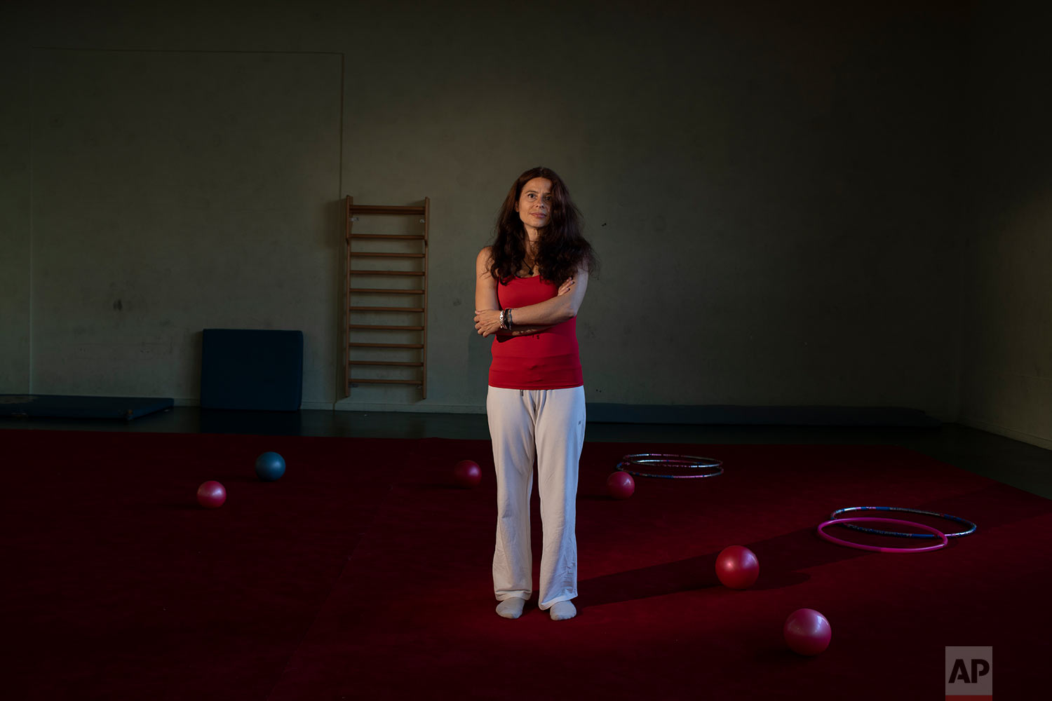 Anna Zeza, a 43-year-old physical education teacher poses for a photo inside a gum of a school in Athens. (AP Photo/Petros Giannakouris)