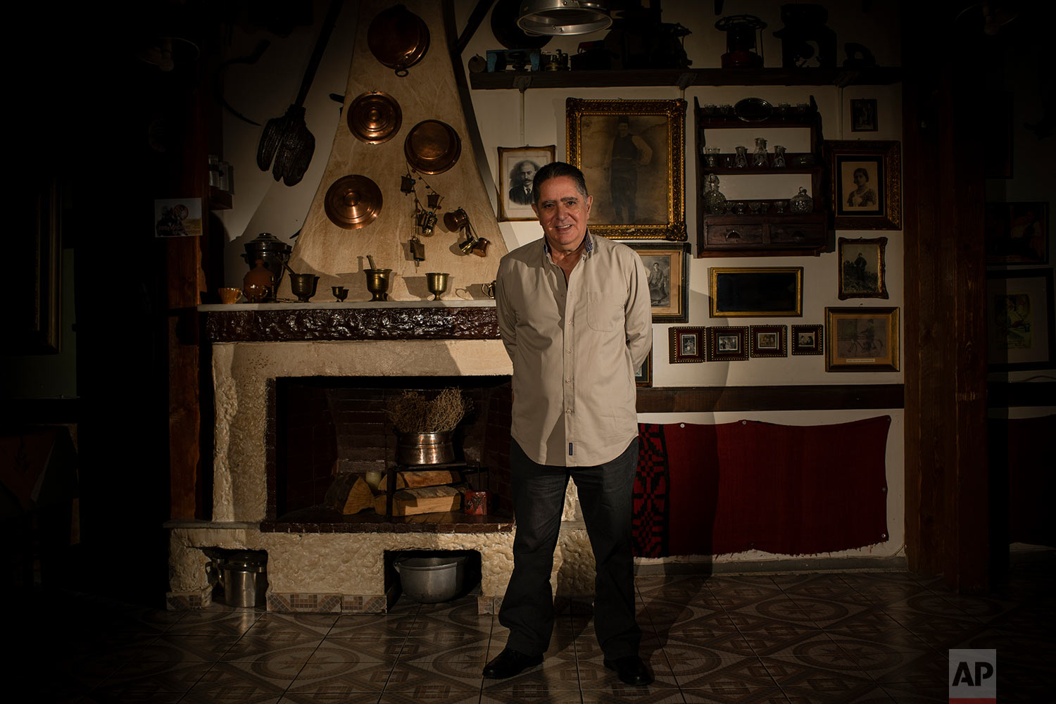 Giannis Grillis, a 67-year-old pensioner, poses for a photo in Athens inside his traditional tavern, which is now run by his children. (AP Photo/Petros Giannakouris)