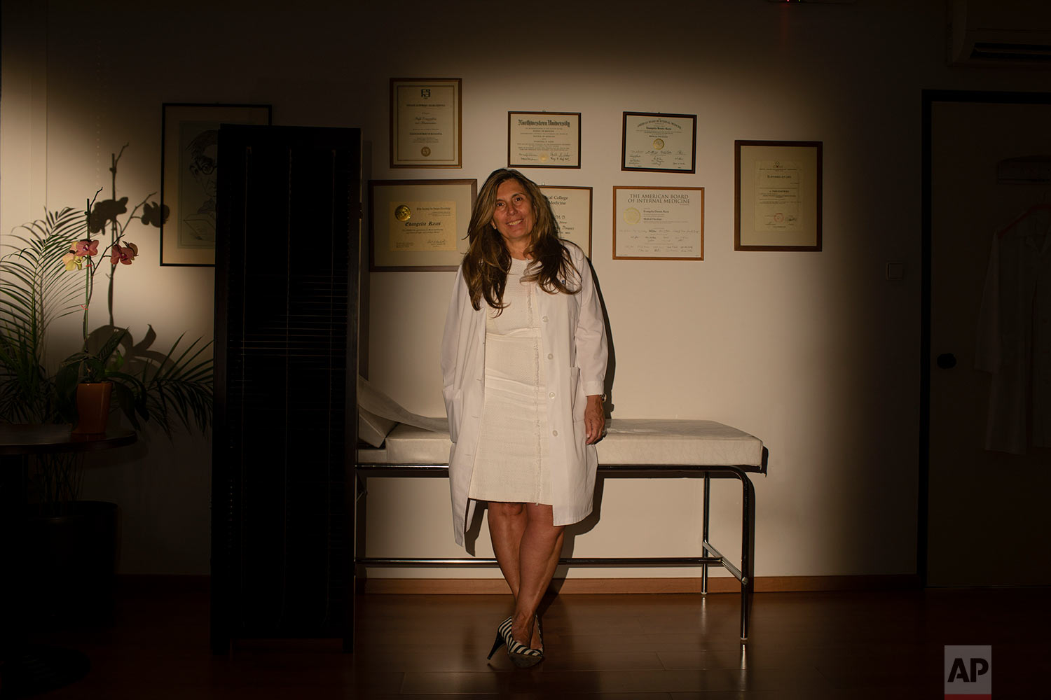 Evi Razi, a 55- year-old oncologist poses for a photo inside her office in Athens. Greece finds itself at a political turning point ahead of Sunday's national elections. (AP Photo/Petros Giannakouris)