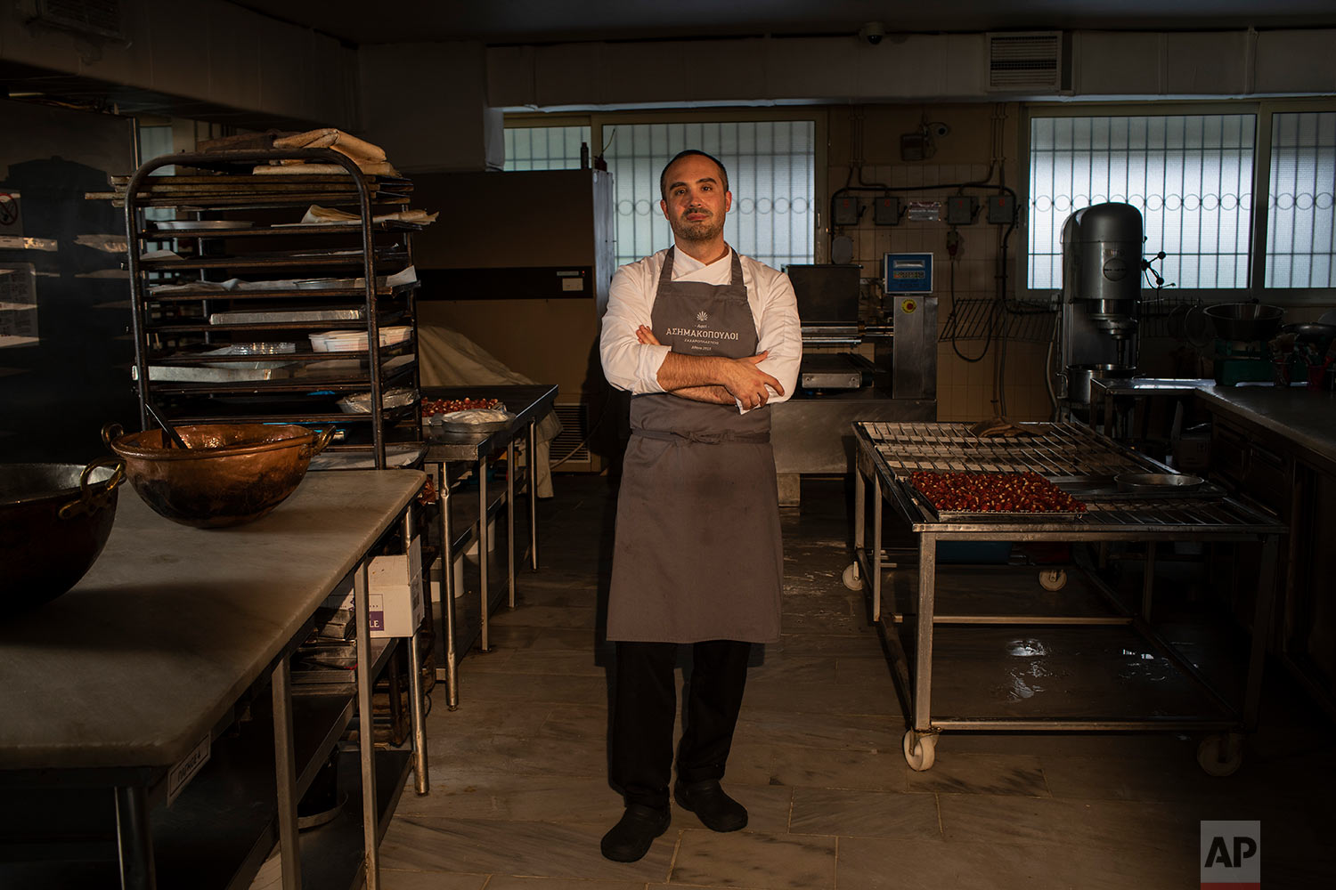 Vasilis Asimakopoulos, a 36-year-old head of pastry production, poses for a photo in his family's patisserie workshop in Athens. (AP Photo/Petros Giannakouris)