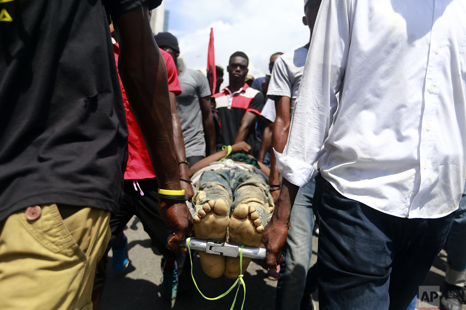 Protesters carry the body of man toward police, who they blame for his death, during an anti-government demonstration in Port-au-Prince, Haiti, Sunday, June 9, 2019. Protesters denouncing corruption paralyzed much of the capital as they demanded the removal of President Jovenel Moise. (AP Photo/Dieu Nalio Chery)