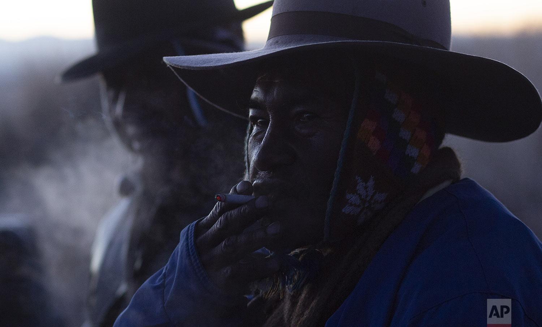"An Aymara Indian smoke a cigarette during the New Year's ritual at the ruins of Lukurmata, Bolivia, early Friday, June 21, 2019. Aymara indigenous communities are celebrating the Andean new year 5,527 or ""Willka Kuti"" (return of the sun in Aymara). (AP Photo/Juan Karita)"