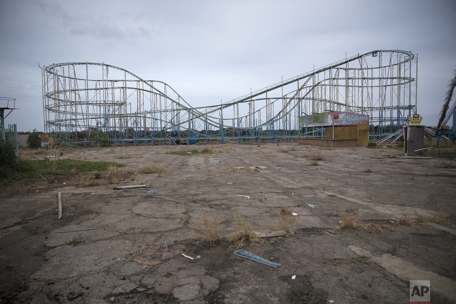 """A roller coaster stands tall in the abandoned amusement park coined """"Diversions Grano de Oro"""" in Maracaibo, Venezuela, May 23, 2019. Much of Venezuela is in a state of decay and abandonment, brought on by shortages of things that people need the most: cash, food, water, medicine, power, gasoline. (AP Photo/Rodrigo Abd)"""